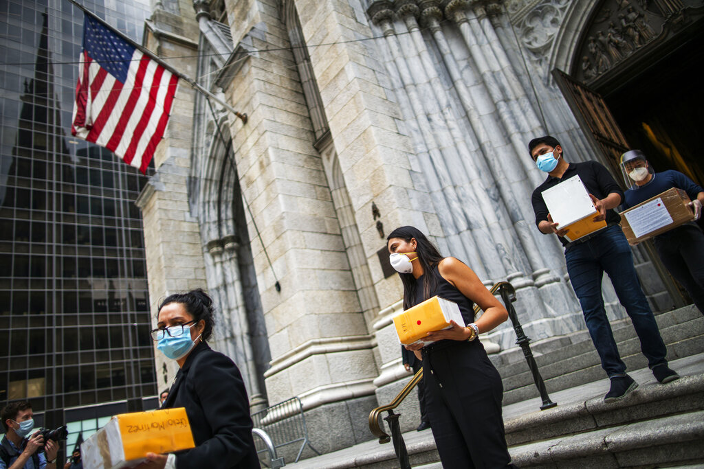In this July 11, 2020, file photo, mourners carry out the remains of loved ones following the blessing of the ashes of Mexicans who died from COVID-19 at St. Patrick's Cathedral in New York.