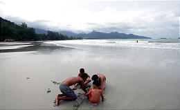 Young tourists play on a deserted beach on the island of Koh Chang in southern Thailand.