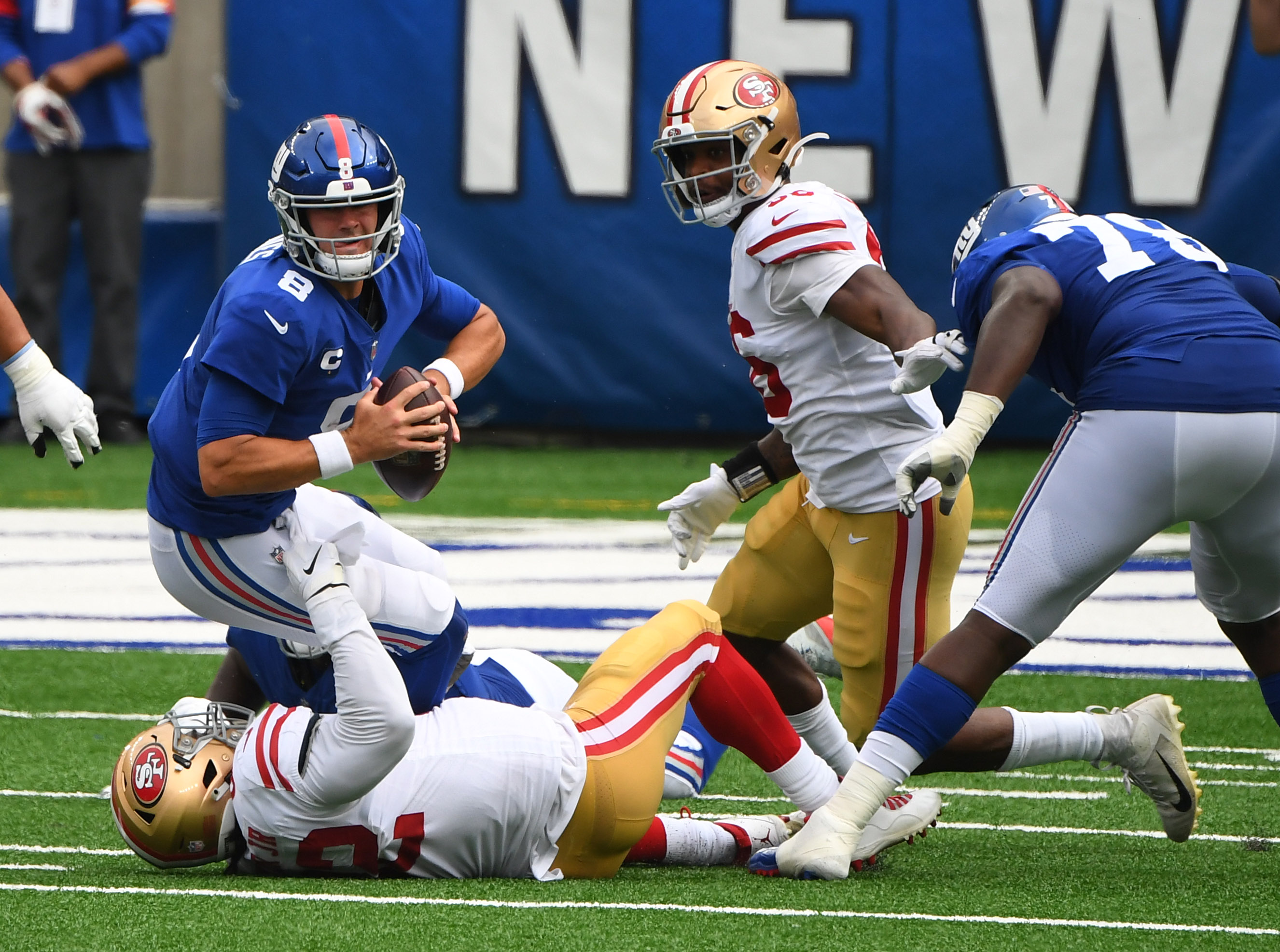 New York Giants quarterback Daniel Jones is sacked by San Francisco 49ers defensive end Kerry Hyder during the third quarter of a NFL football game at MetLife Stadium.
