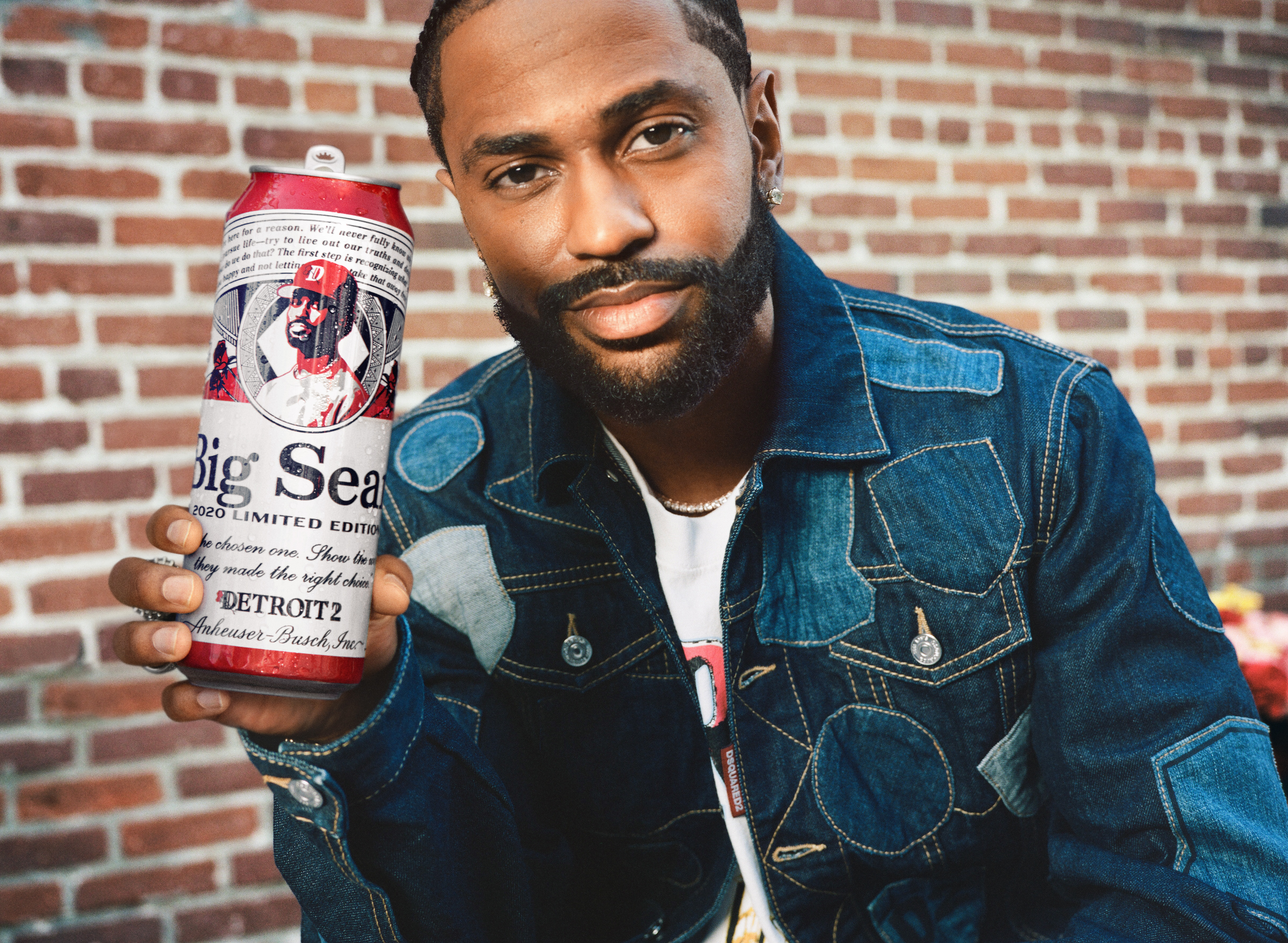 Big Sean wears a jean jacket and holds up a tall boy with his face on it.