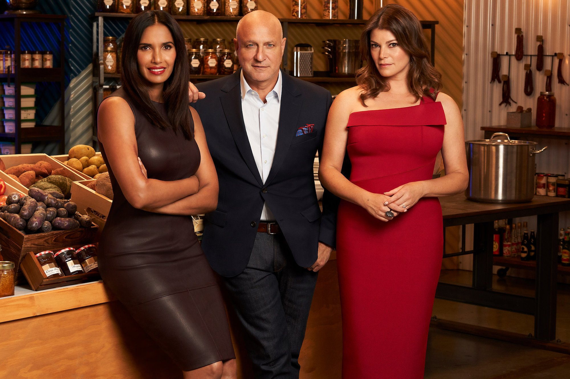 Padma Lakshmi, Tom Colicchio and Gail Simmons pose in front of crates of produce and wine for a Top Chef promo photo.