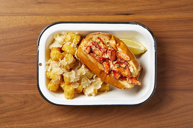 A white tin dish with a buttery bun filled with chopped lobster meat, a lemon wedge, and tater tots