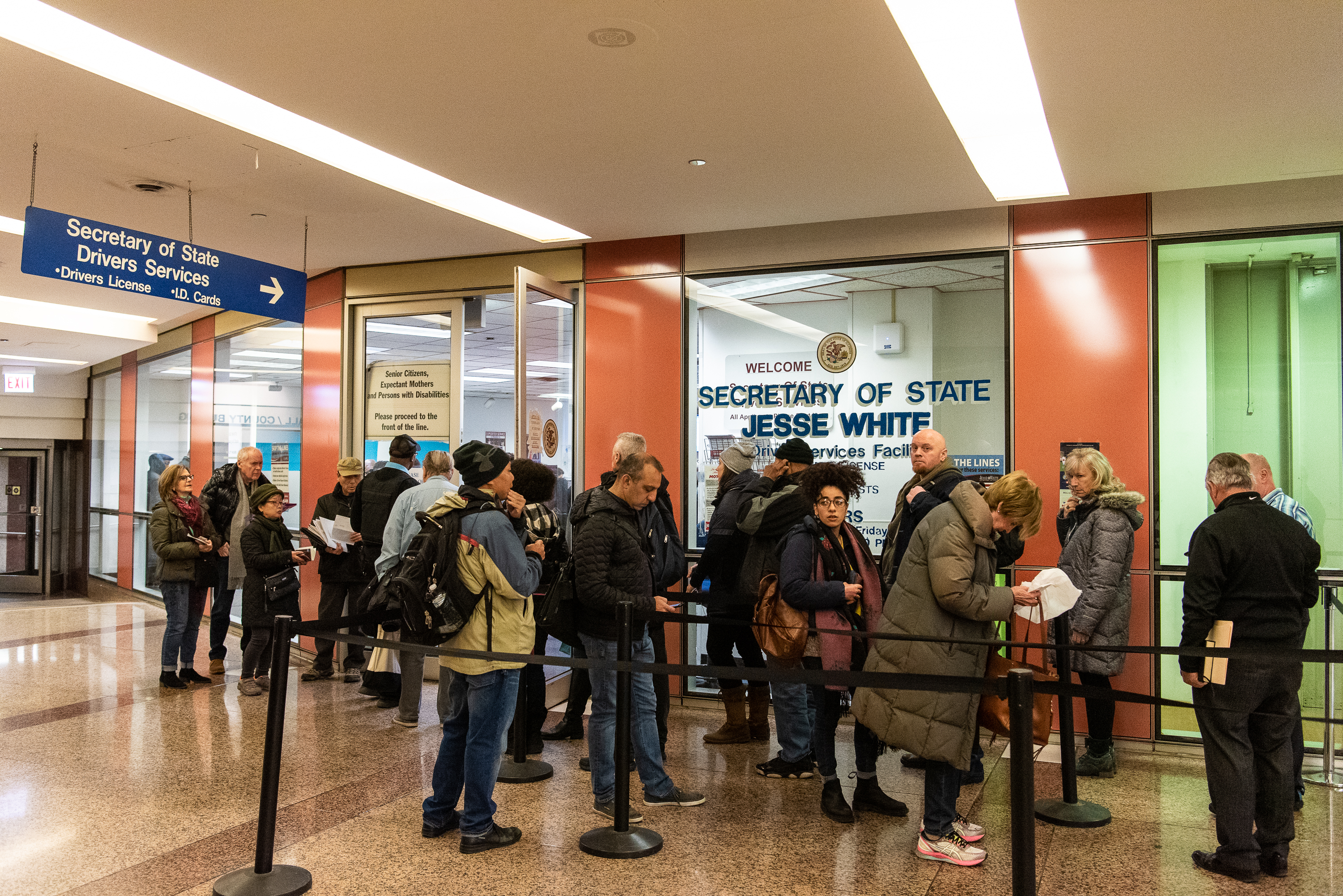 "Dozens of people wait in line at the Secretary of State office inside the Thompson Center, many waiting to get their ""Real ID"" earlier this year."