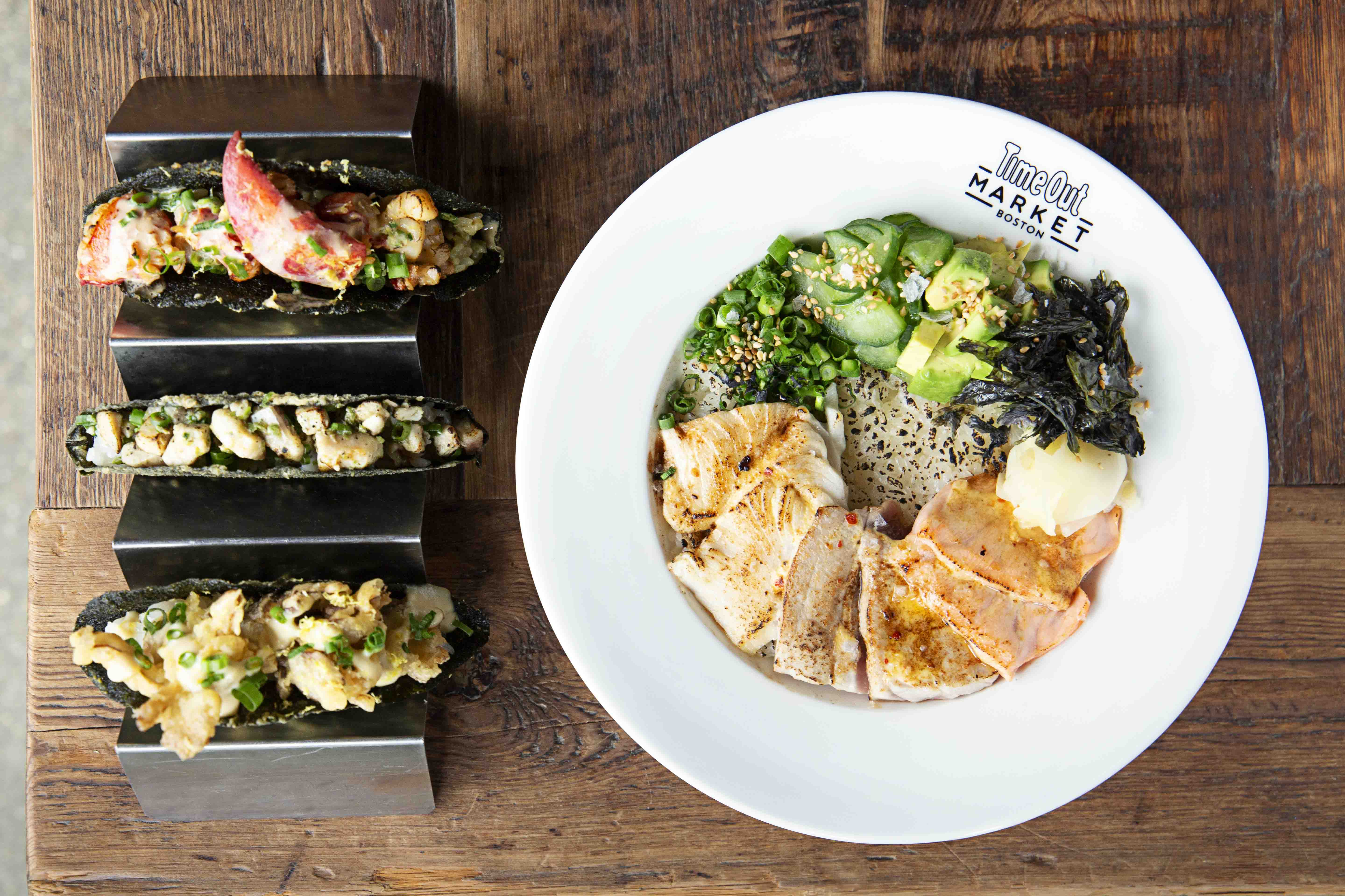 overhead view of a meal on a wooden table: three tacos in crispy nori shells stand up in a taco holder, and a bowl is full of rice, greens, and torched sashimi
