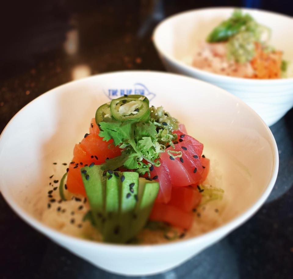 a poke bowl filled with rice, red tuna, avocado and black sesame seeds, topped with cilantro and jalapeños