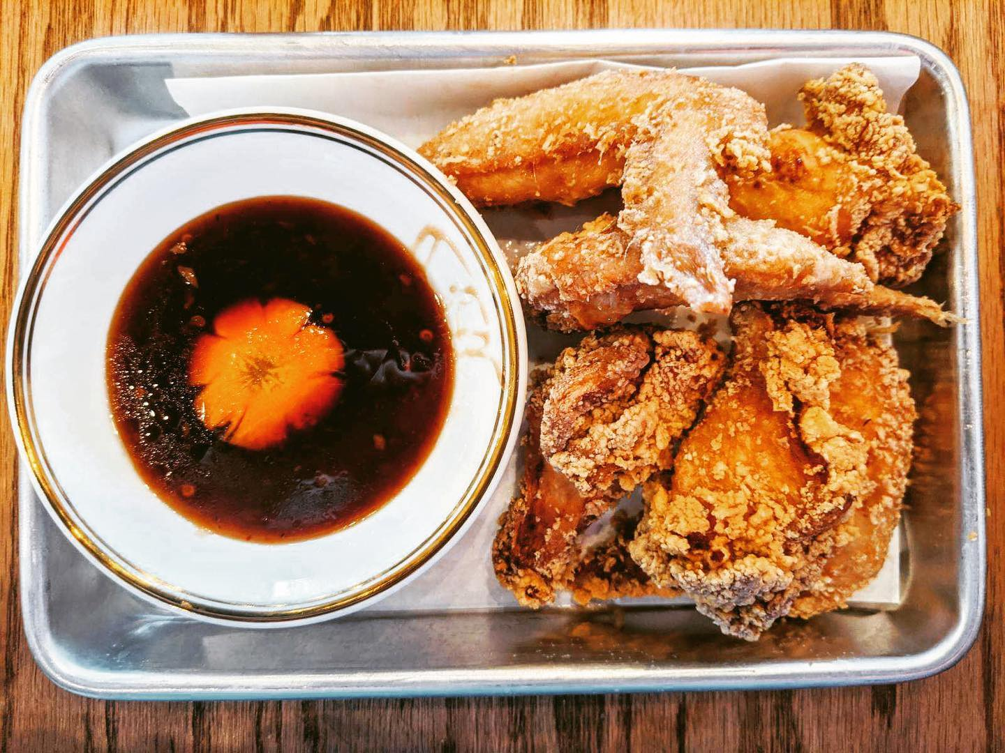 A metal tray with a pile of lightly-battered chicken wings on the right and a deep, rich-looking dipping sauce on the left
