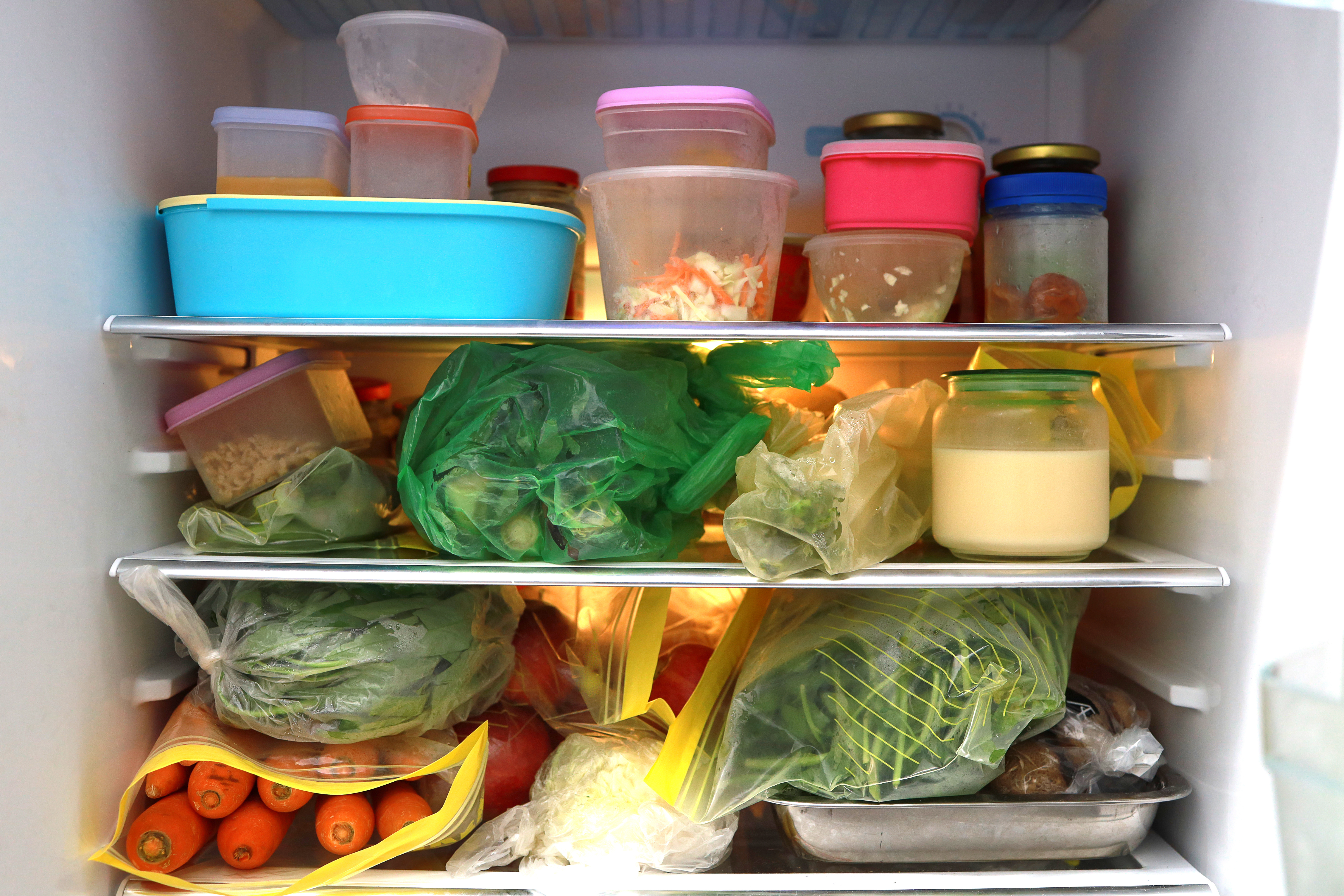 An open fridge with messy shelves