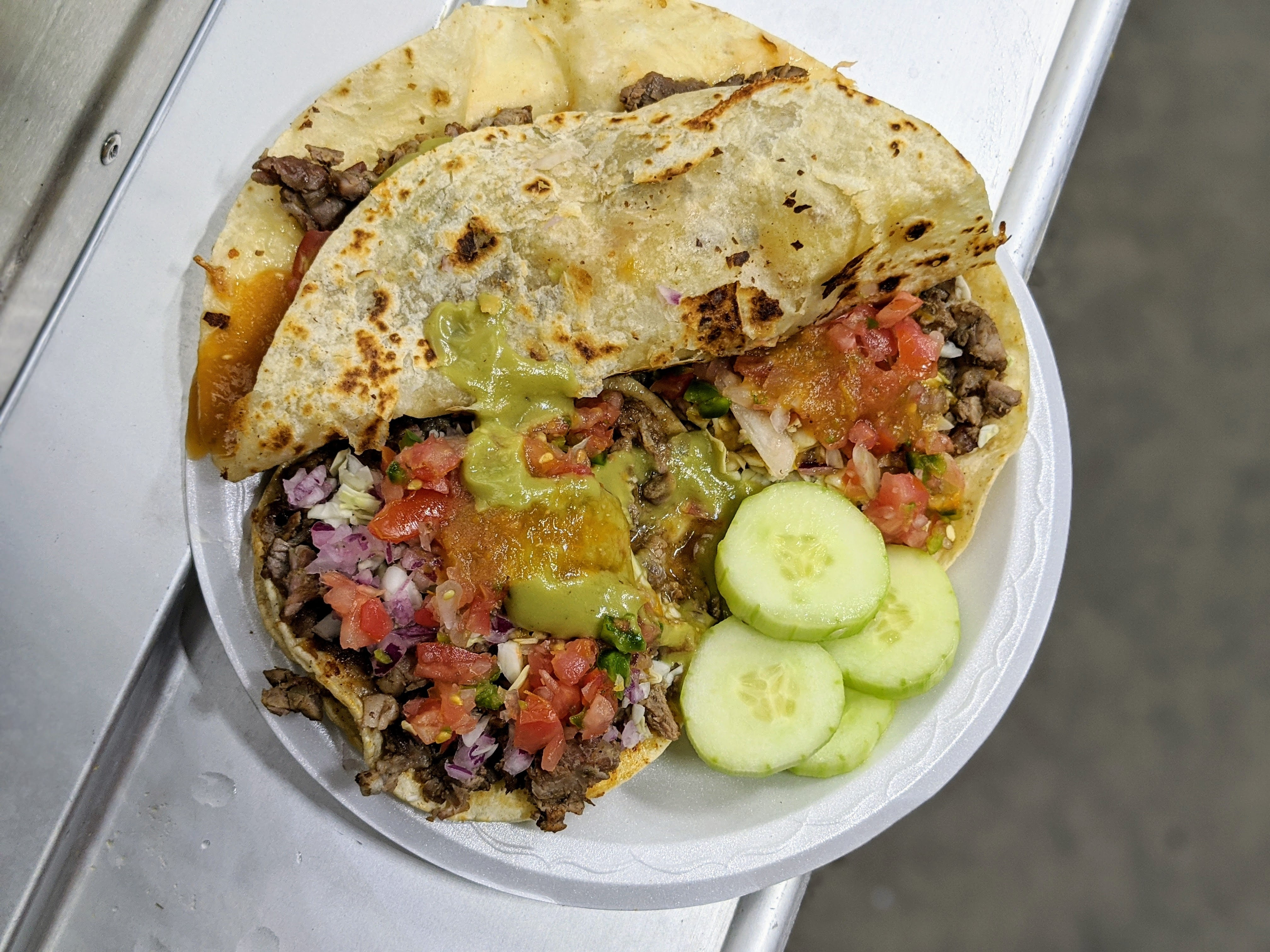 Carne asada tacos and quesadilla from La Carreta on a plastic plate on a food truck in Long Beach