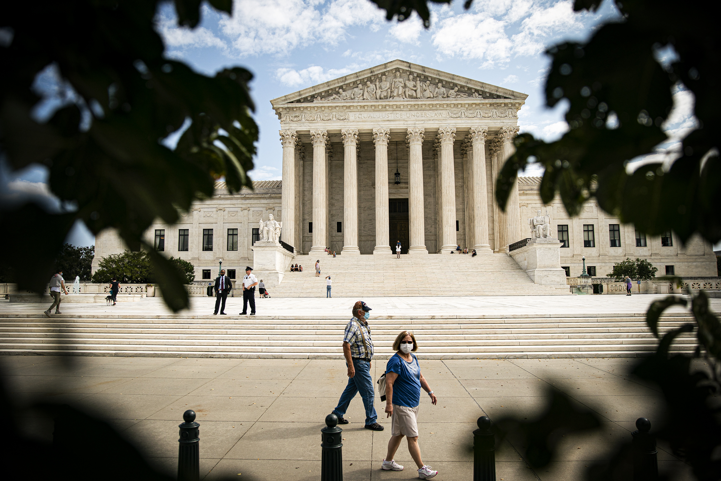 People walk past the US Supreme Court building in Washington, DC