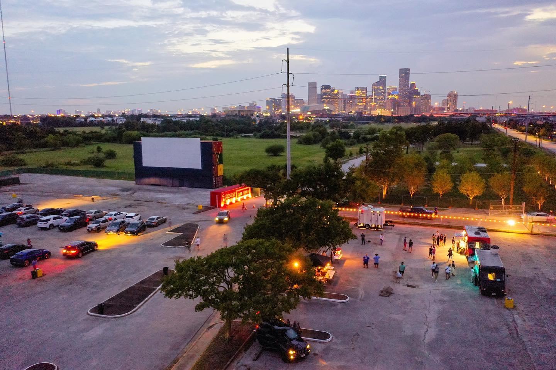 一个大型汽车影院屏幕的无人机视图,汽车停在前面。右侧是一辆快餐车外的人群,背景是休斯顿的日落景观