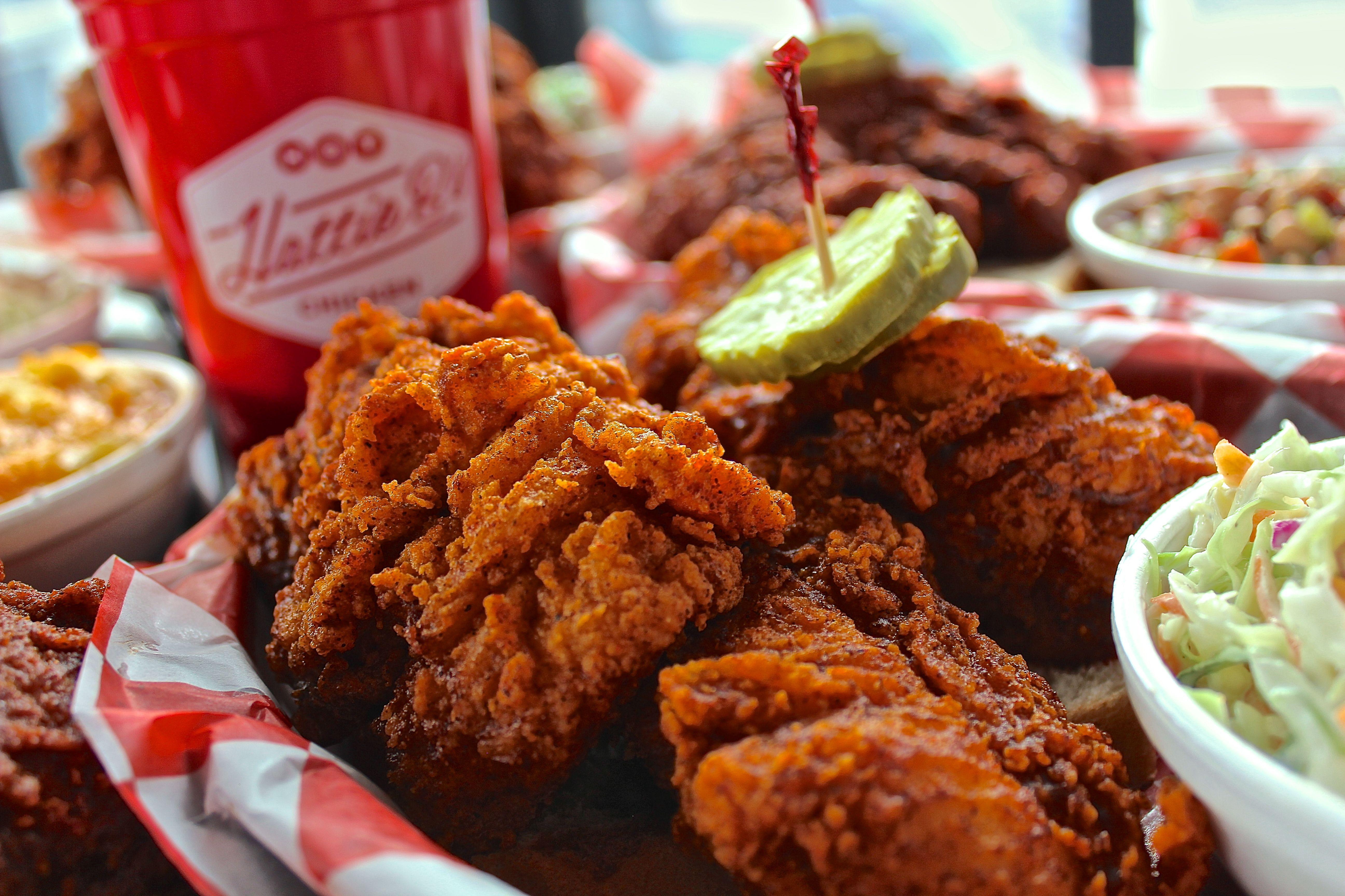 a plate of hot Nashville-style chicken served on red and white checkered paper, with pickles and cole slaw.