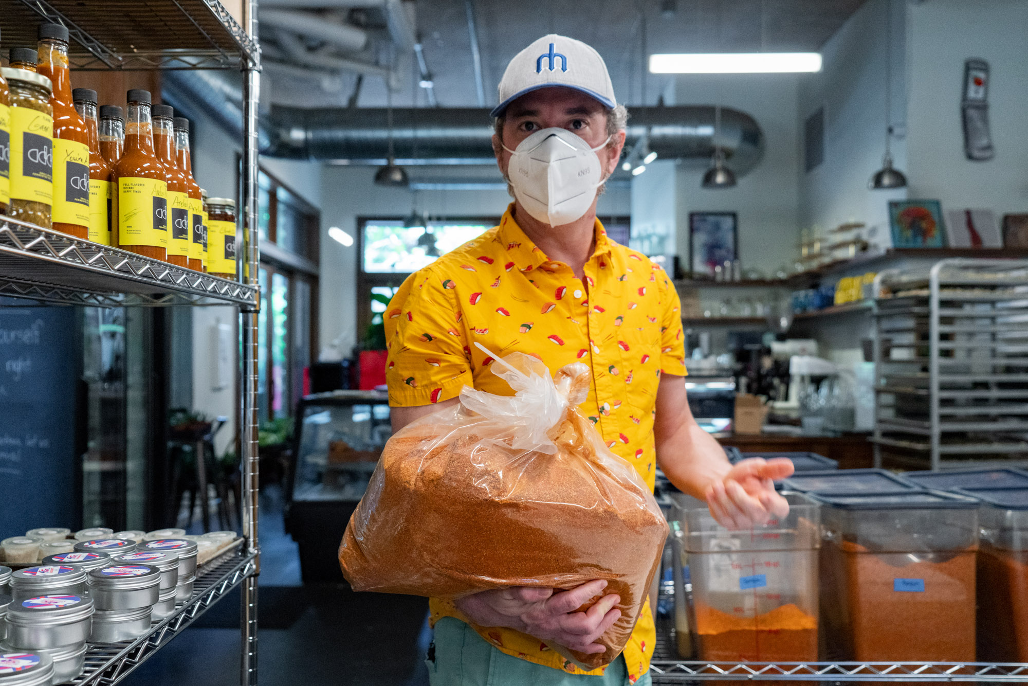 A man wearing a face mask holds a bag of spices