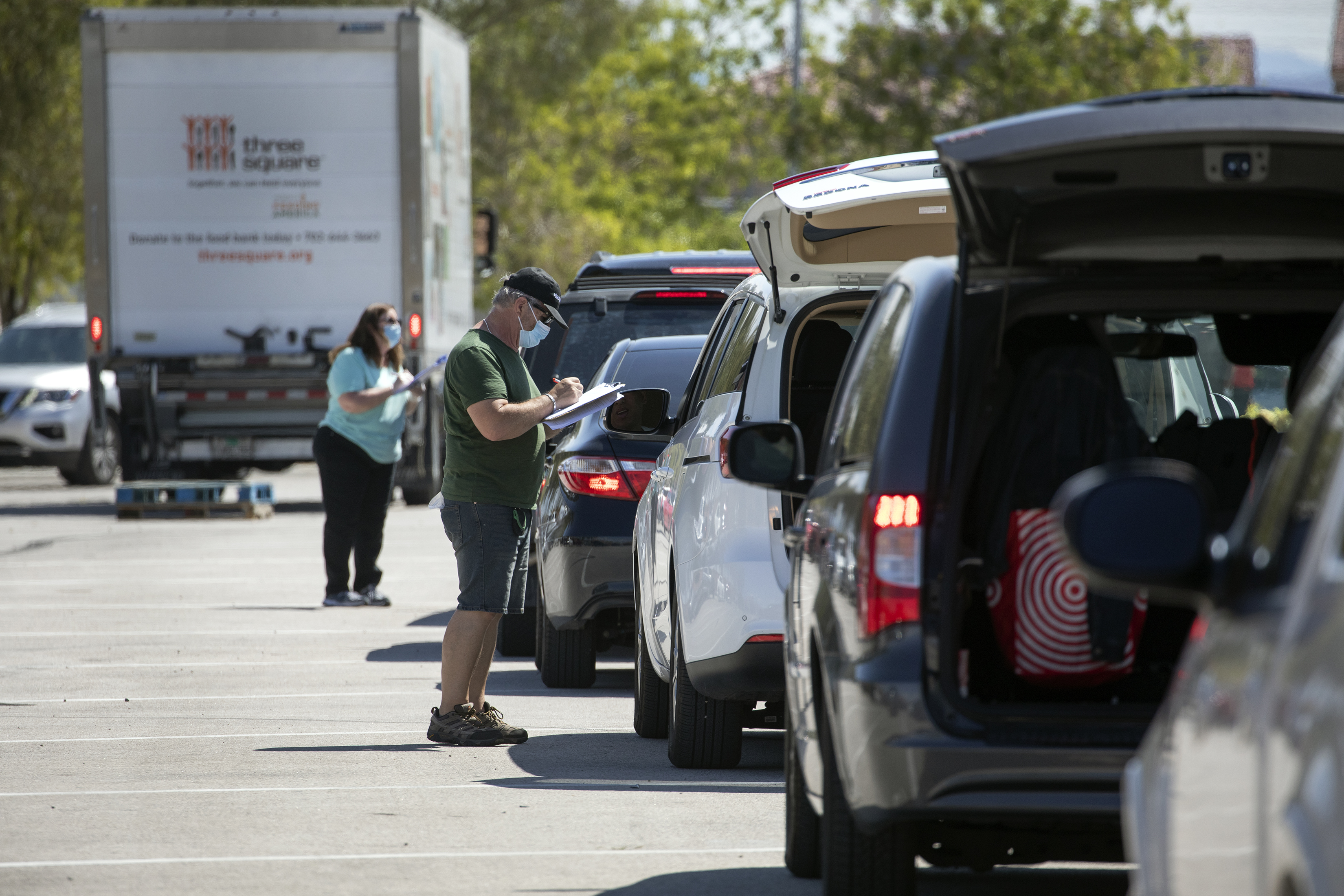 Vehicles line up at a mobile food bank withe their trunks open to receive food