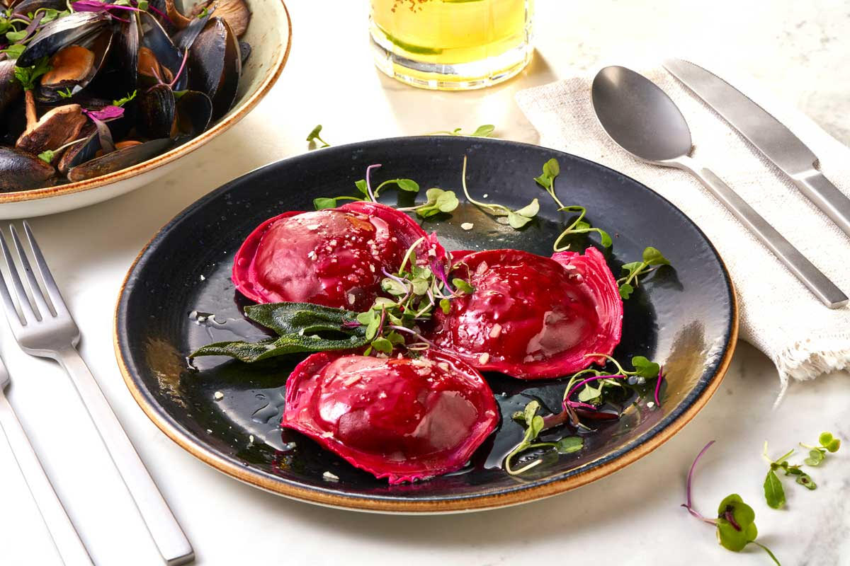 a dark plate topped with three pieces of beet-colored ravioli, topped with a sprinkling of greens
