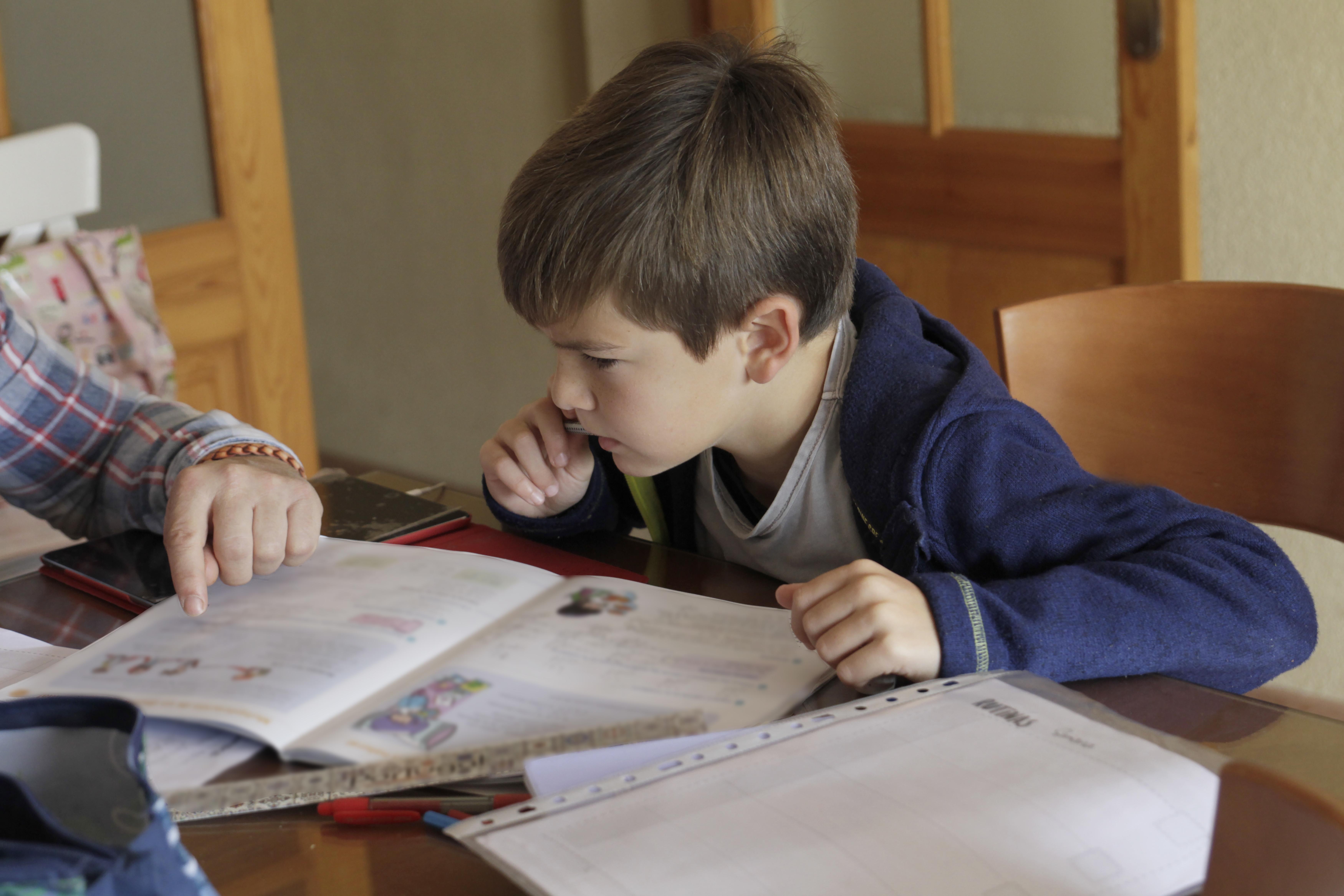 A boy doing school work at a desk.