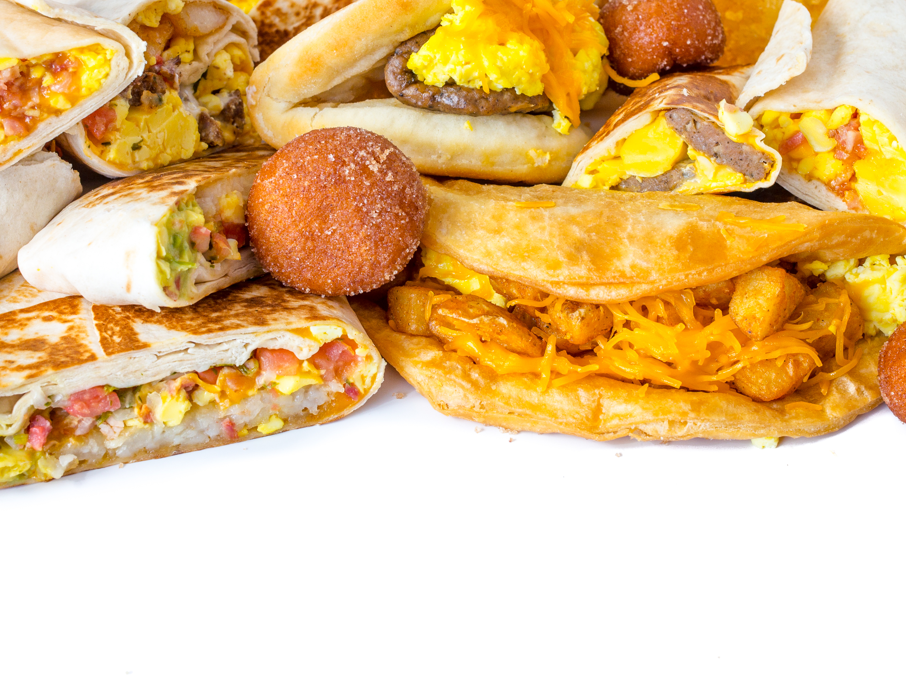 Pile of unwrapped Taco Bell breakfast food.
