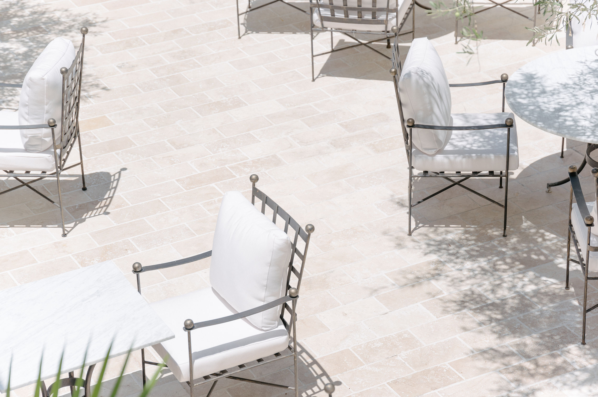 A tan new outdoor patio shown from an angle above, with leafy surroundings and metal seating.
