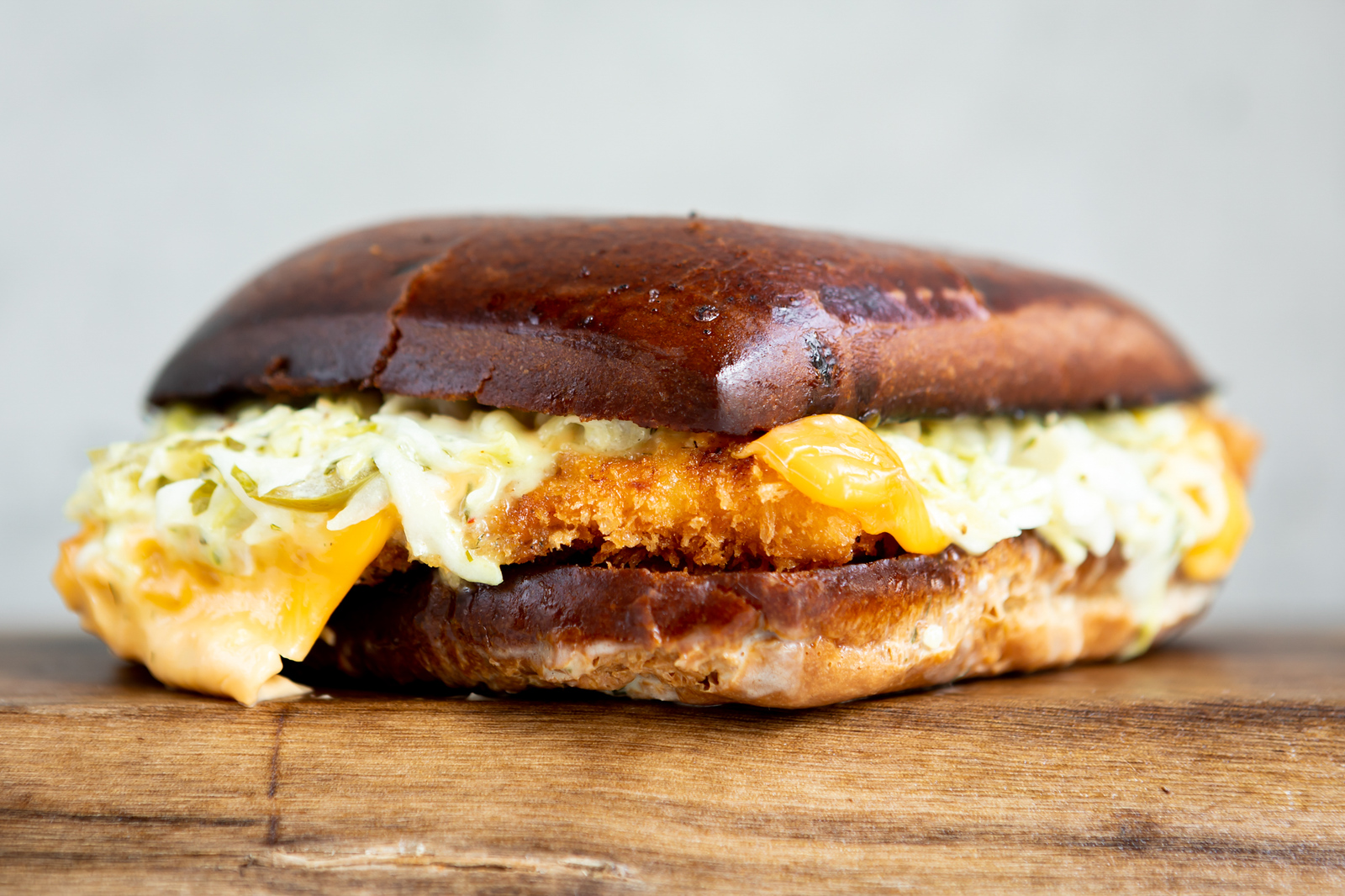 Fried fish sandwich on a square bun, with slaw and melted American cheese spilling out the side