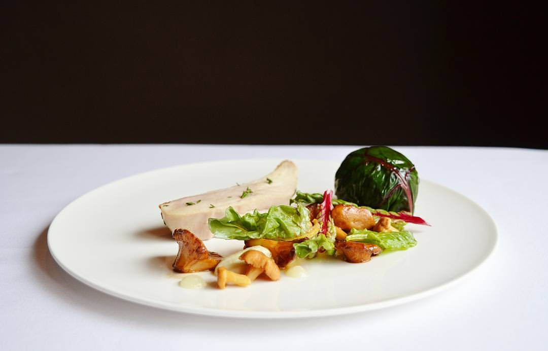 Glamour shot of a fine-dining piece of roast chicken on a white plate with vegetables. The plate sits on a white tablecloth with a black background.