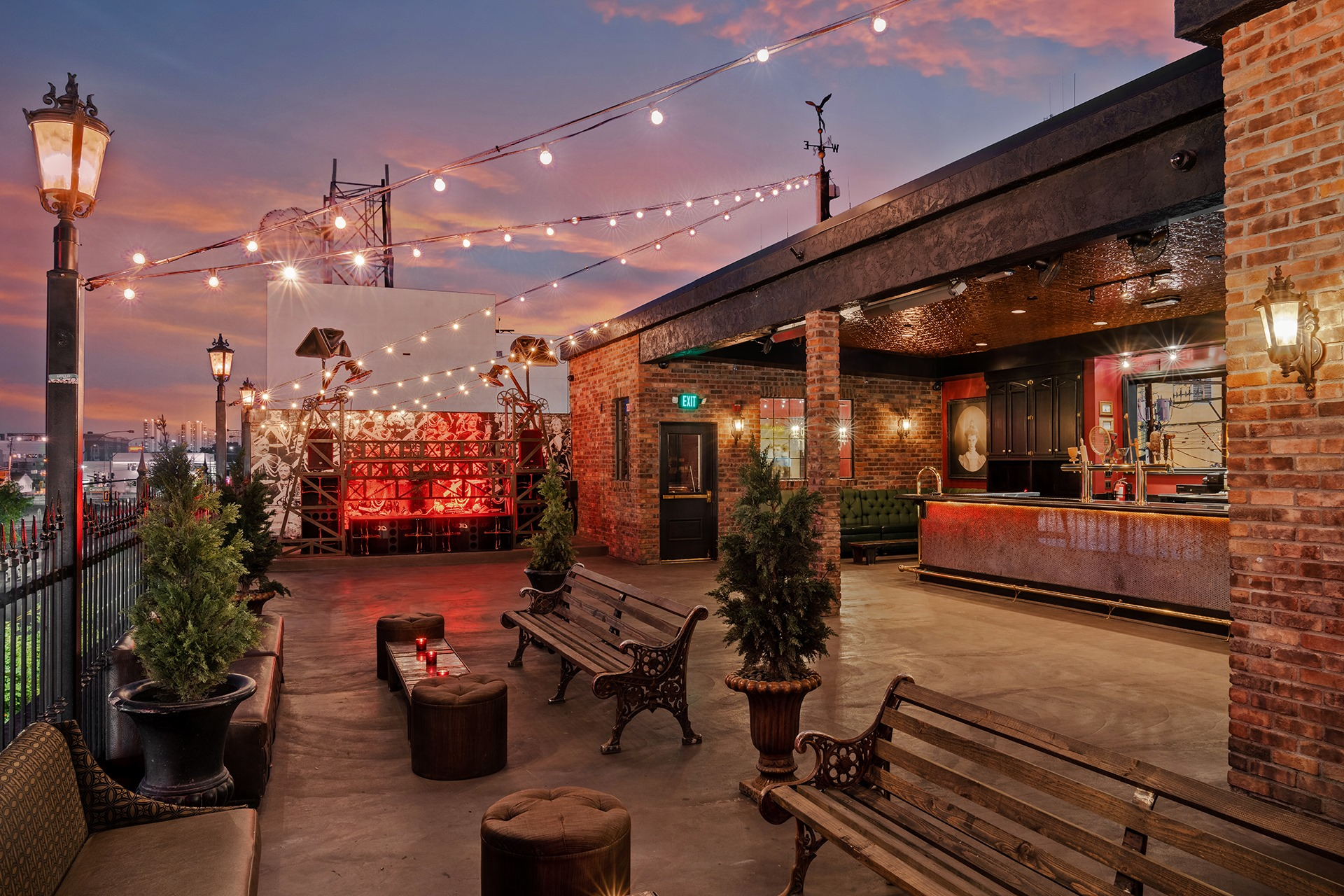 A patio with a covered bar, string lights, and park benches