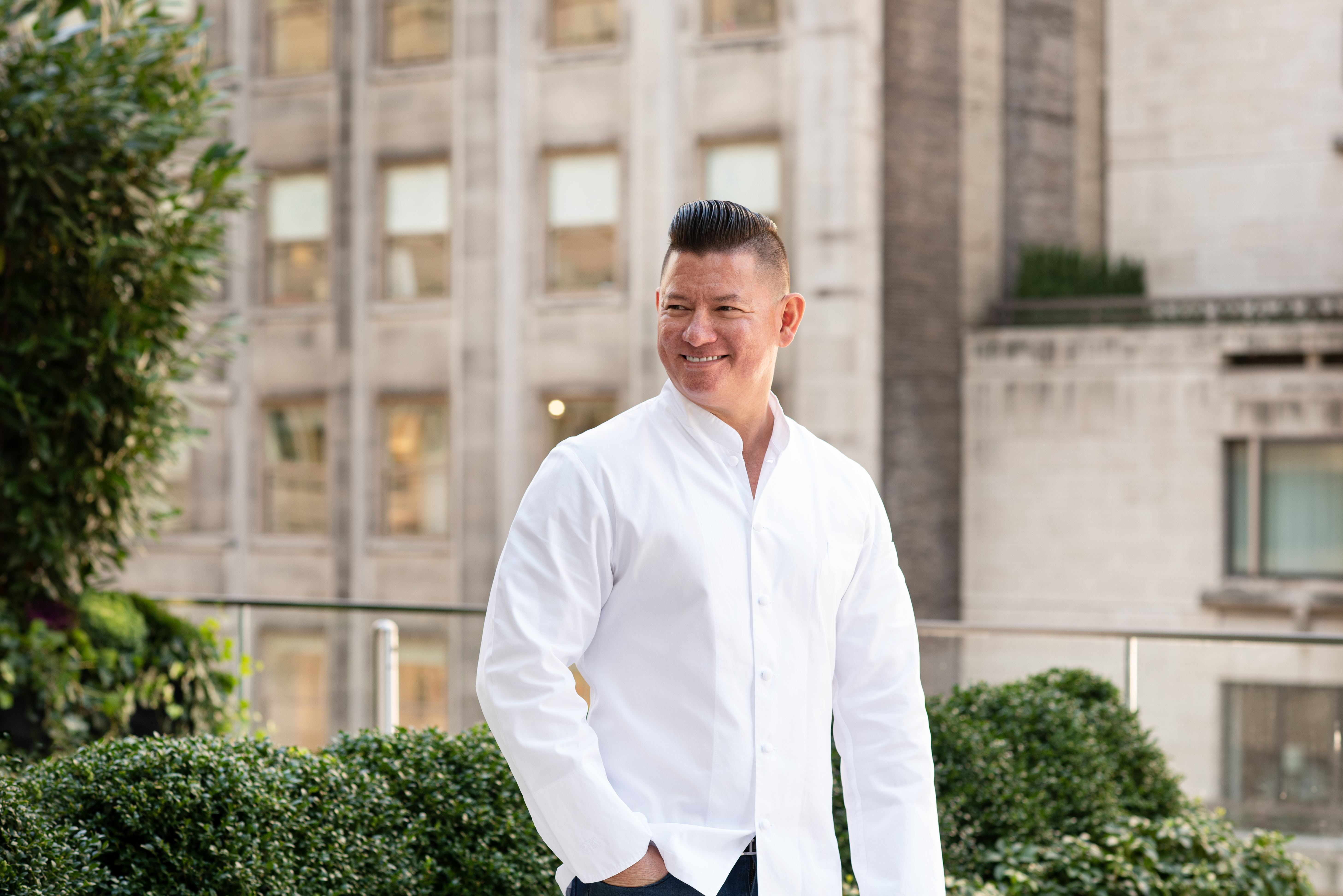 A man in a white shirt smiling and looking away from the camera and standing on a terrace with trees