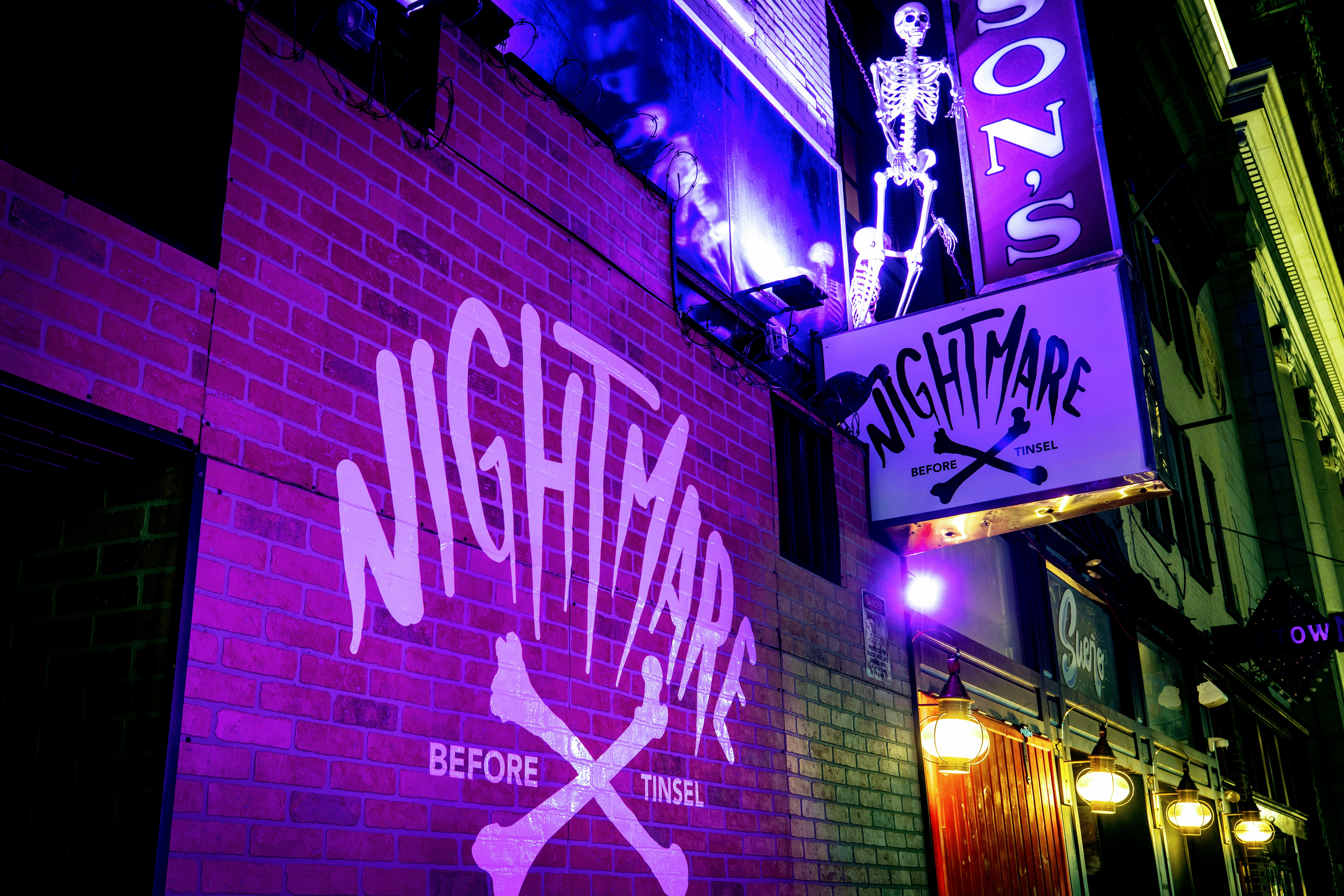 outside of bar with nightmare projected on the brick front, a sign that says nightmare, and a fake skeleton