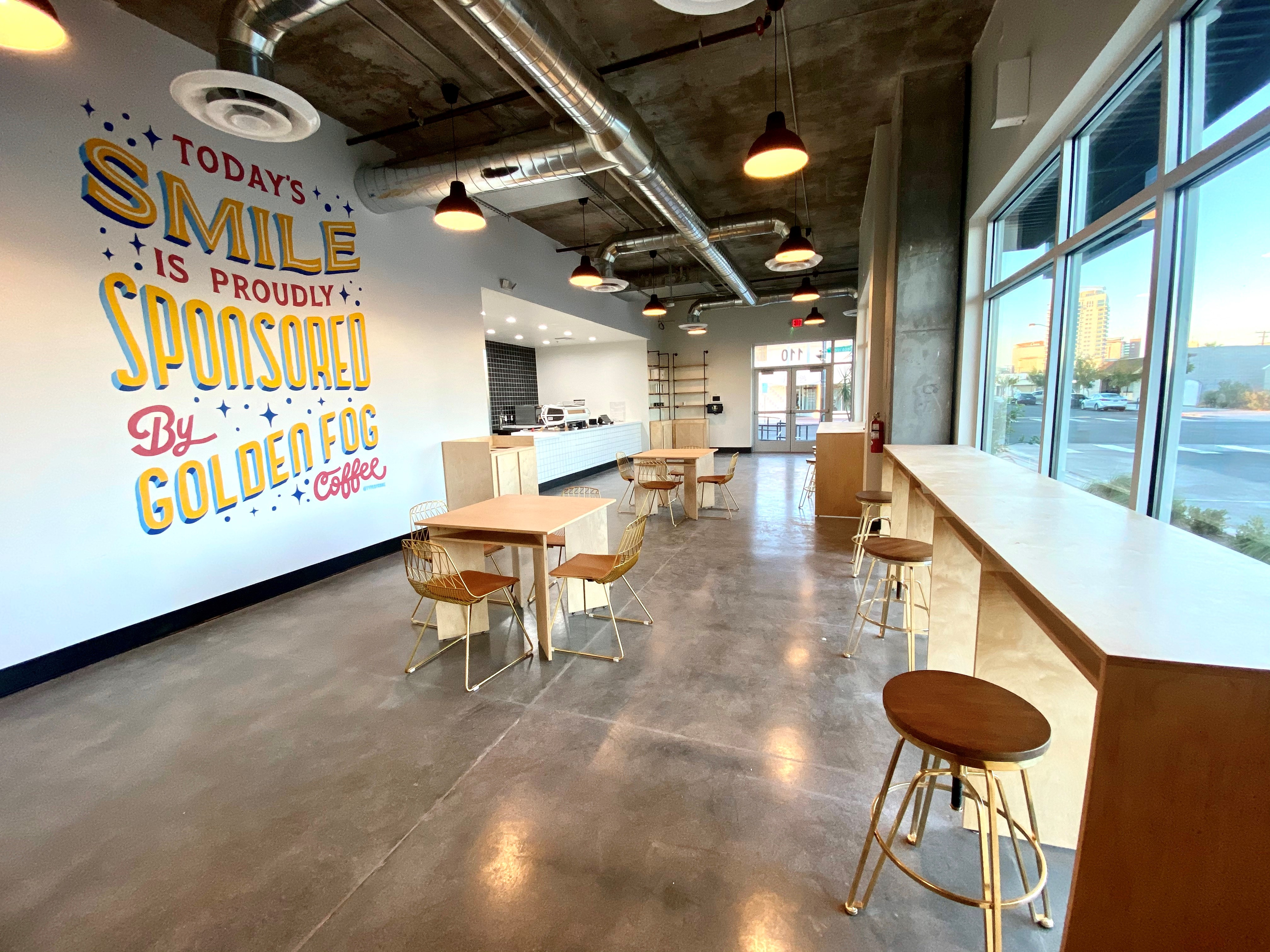 The interior of a coffee shop with wood floors and a mural on the wall.