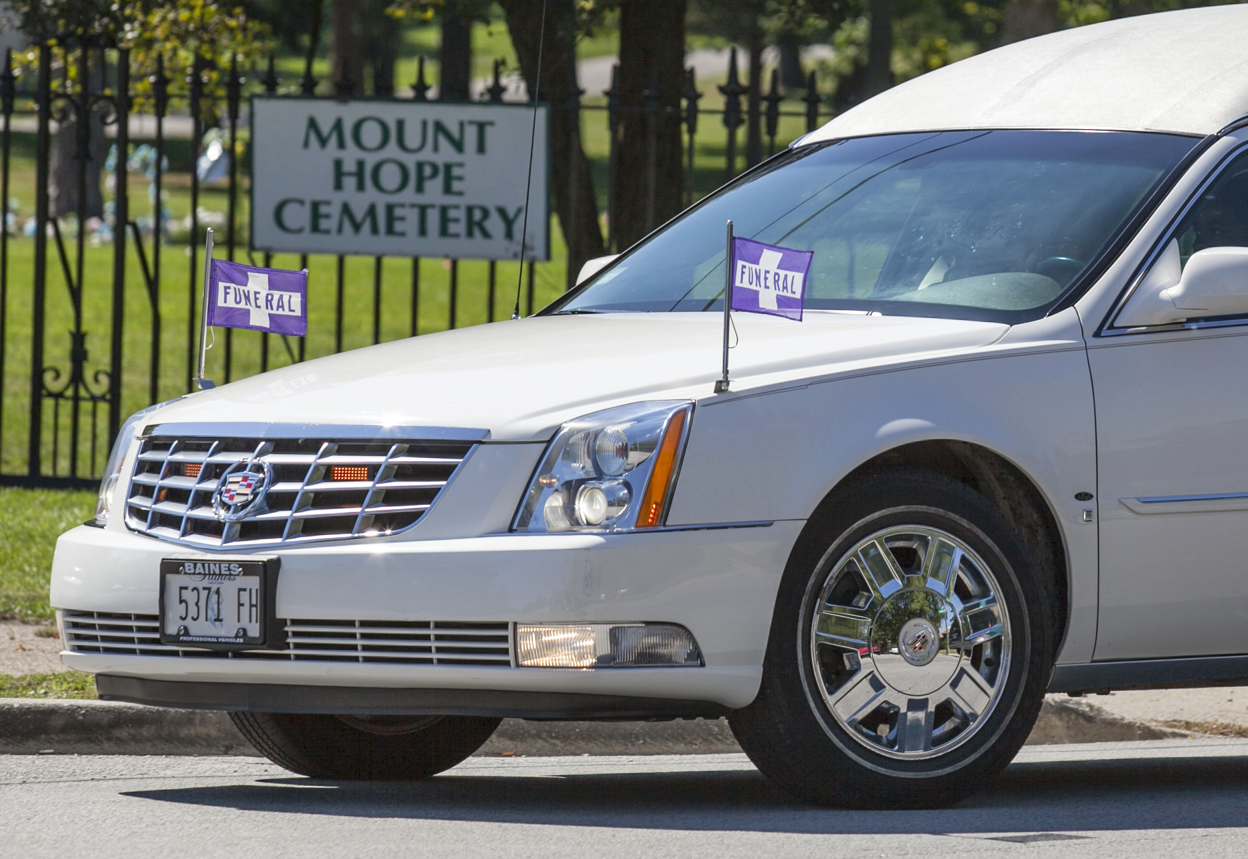 A hearse leads a funeral procession into Mount Hope Cemetery, on Saturday, September 15, 2012.