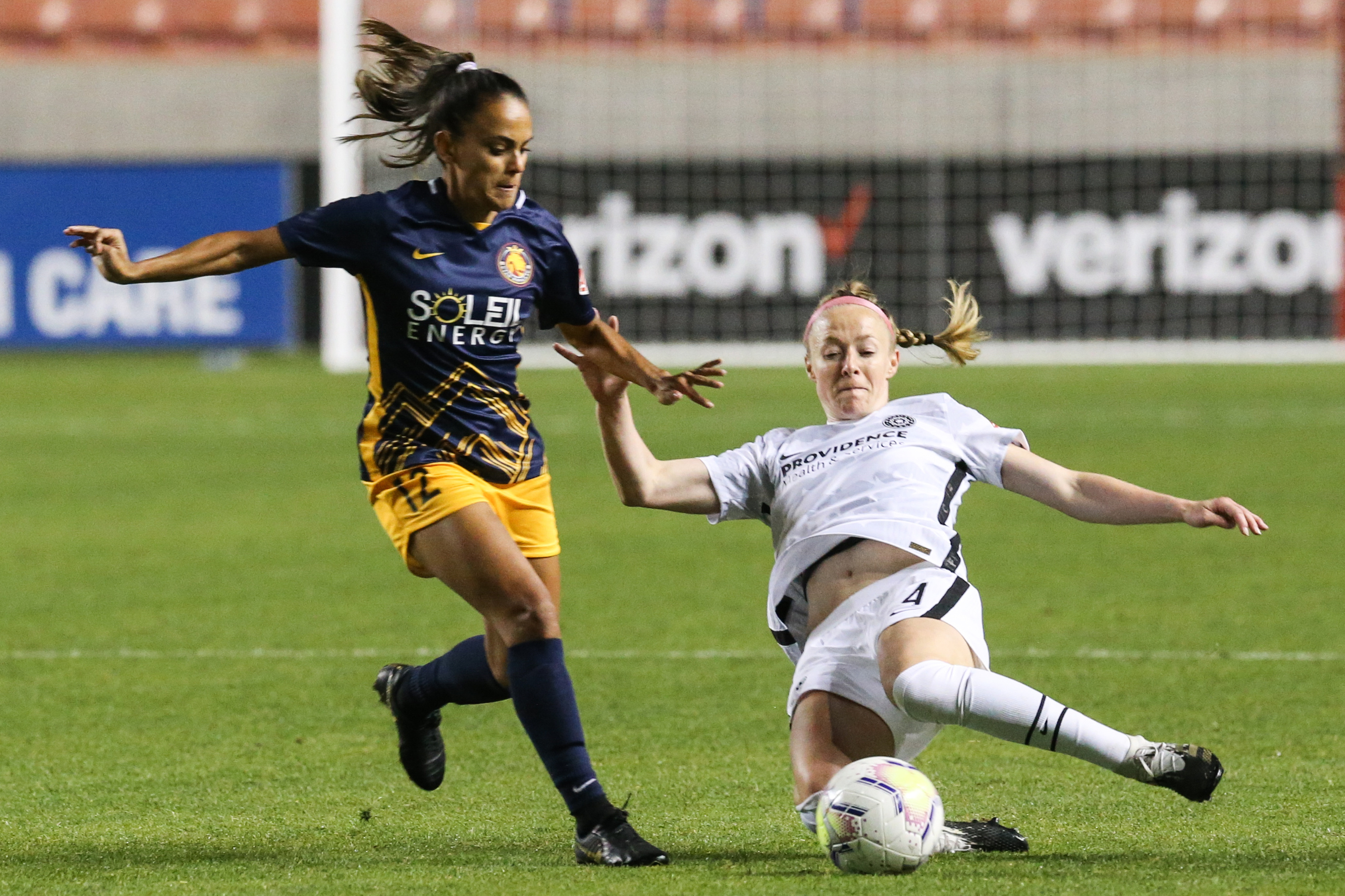 Portland Thorns FC defender Emily Menges (4) makes a slide tackle against Utah Royals FC midfielder Taylor Lytle (12) during an NWSL soccer game at Rio Tinto Stadium in Sandy on Saturday, Oct. 3, 2020.