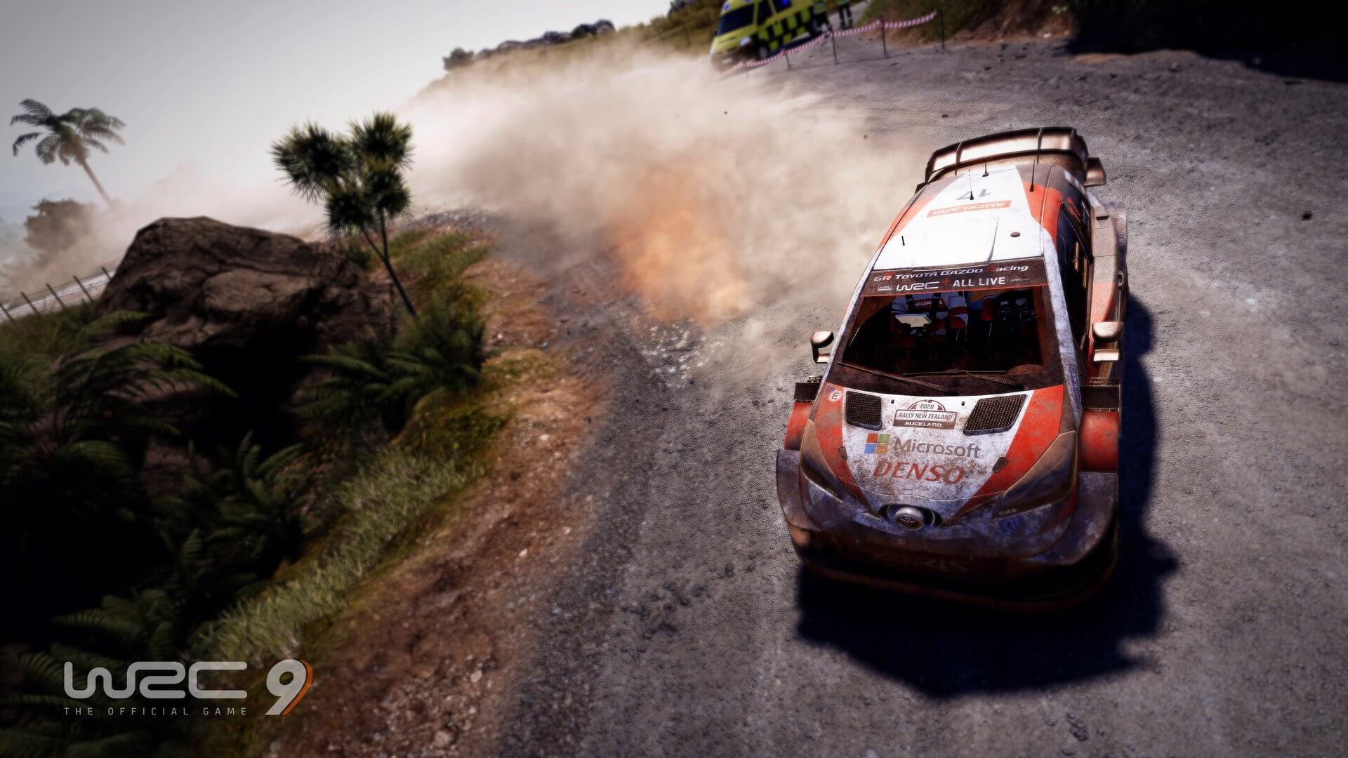 a dirty rally car, trailing dust from a gravel road, slides through a turn