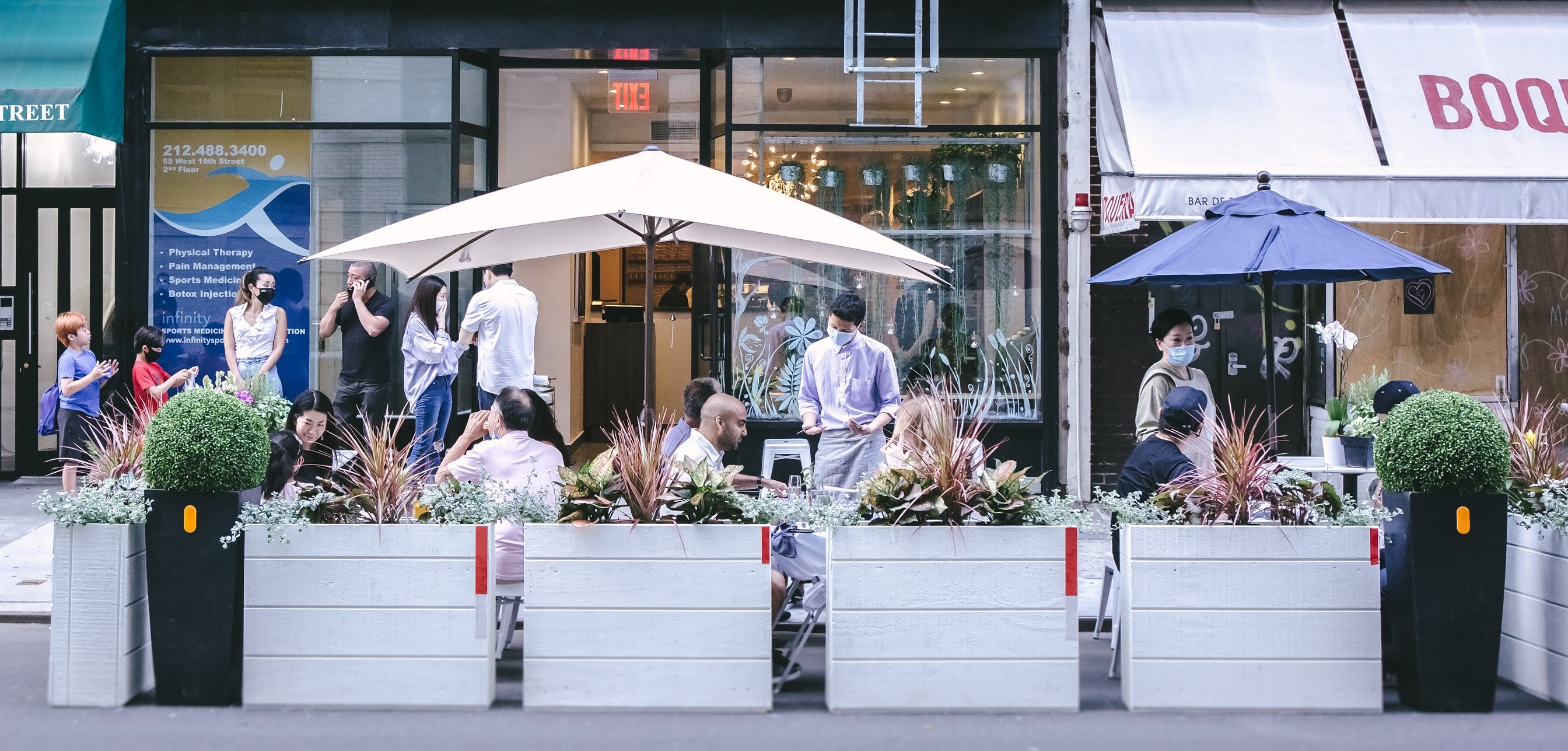 A server taking an order from customers sitting at tables and chairs set up outside of Maki Kosaka.