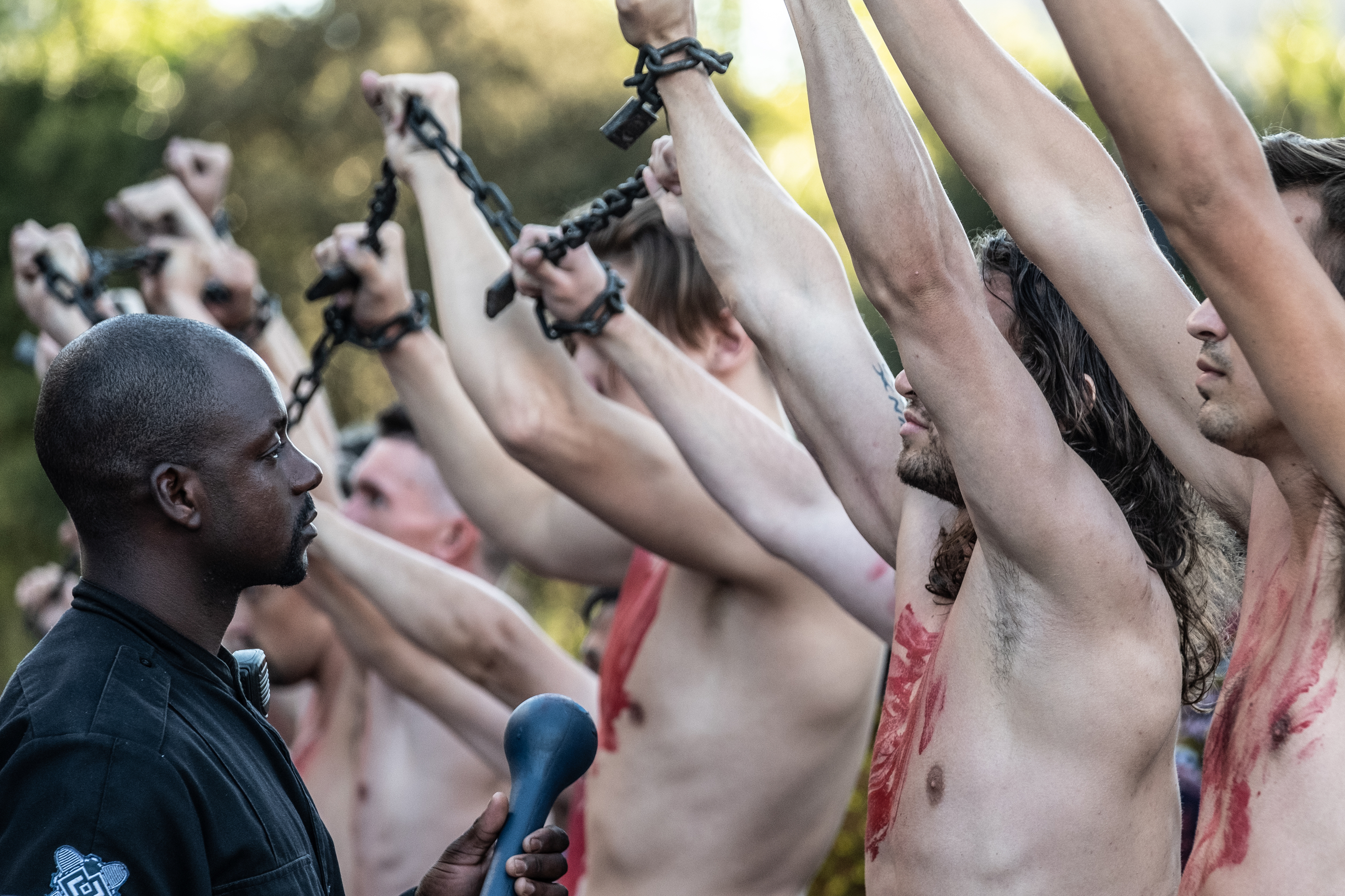 A uniformed Black agent examines a line of chained, shirtless white men in Noughts + Crosses