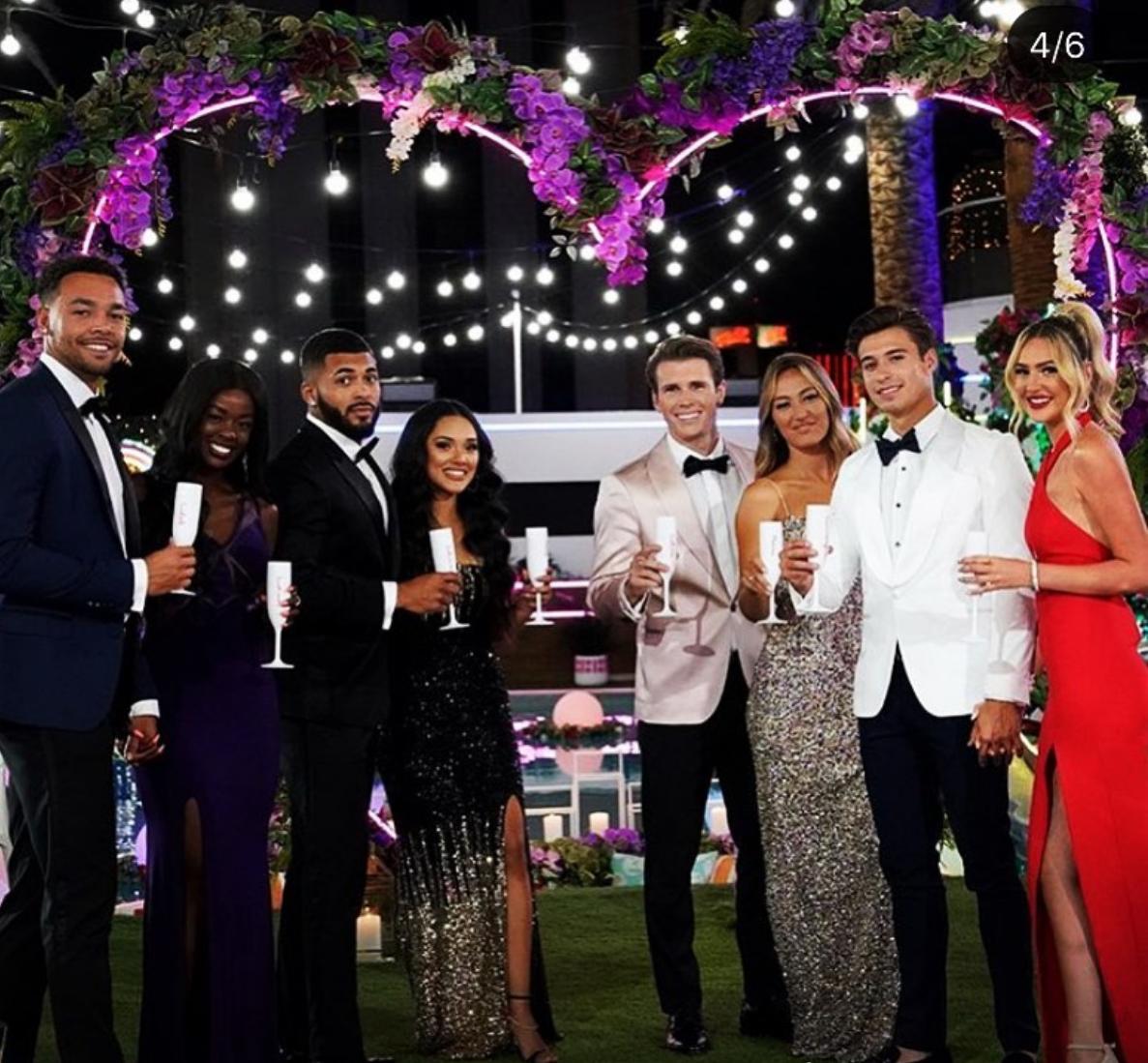 Four men and four women in black tie attire hold Champagne glasses