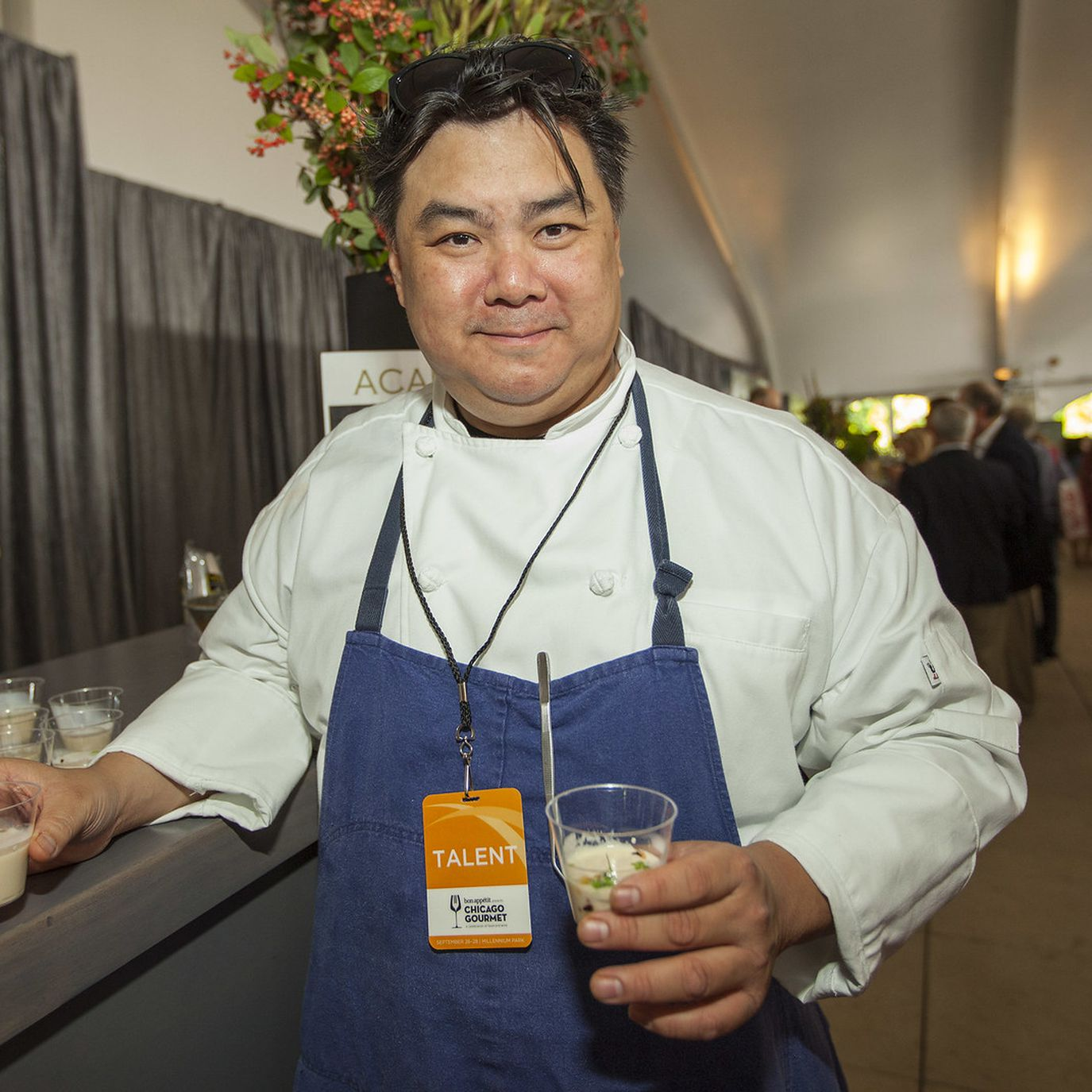 A chef leaning on a table with a drink in his hand wearing a blue apron.