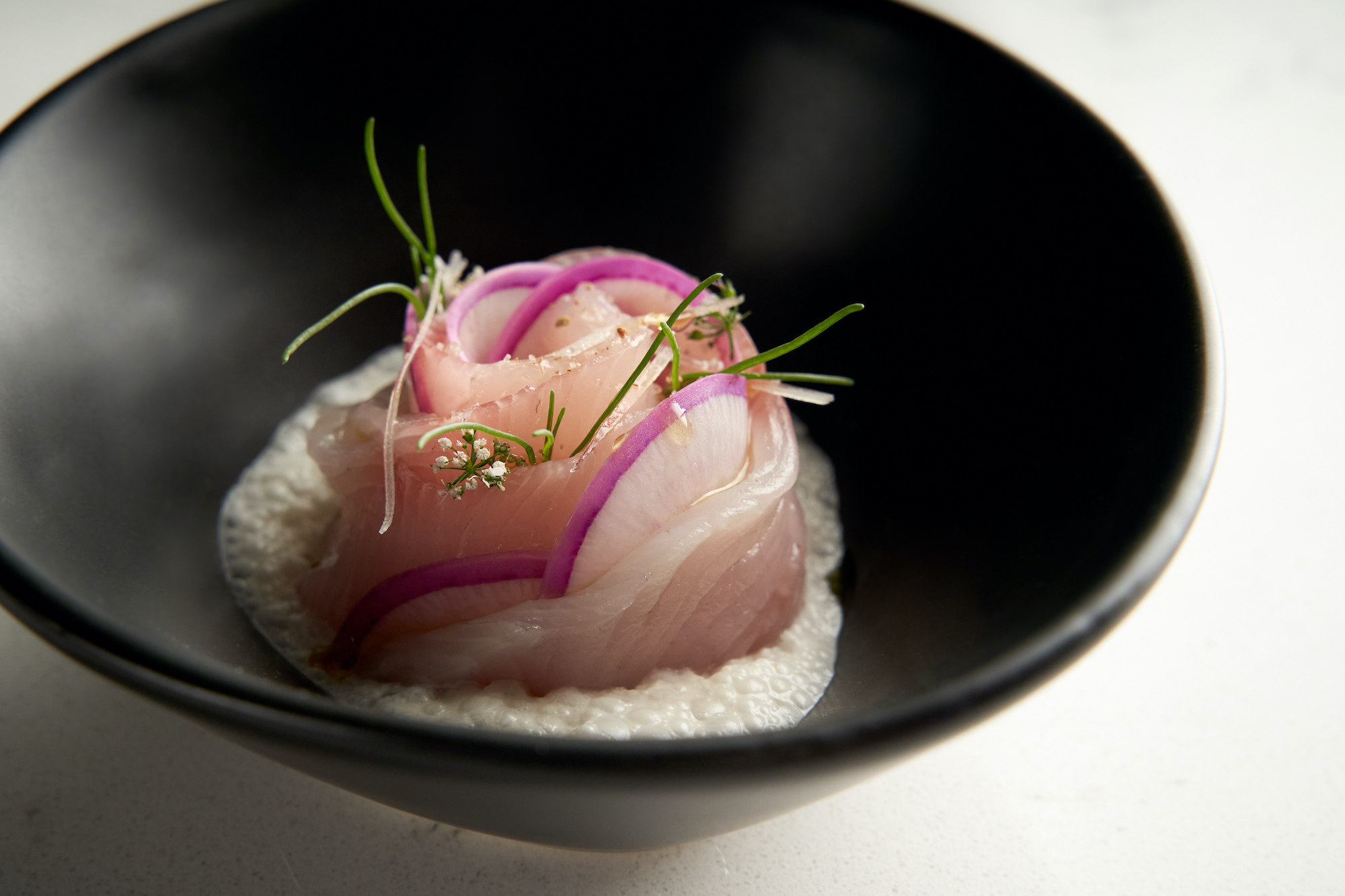 A tight coil of raw fish served as a crudo in a dark bowl.