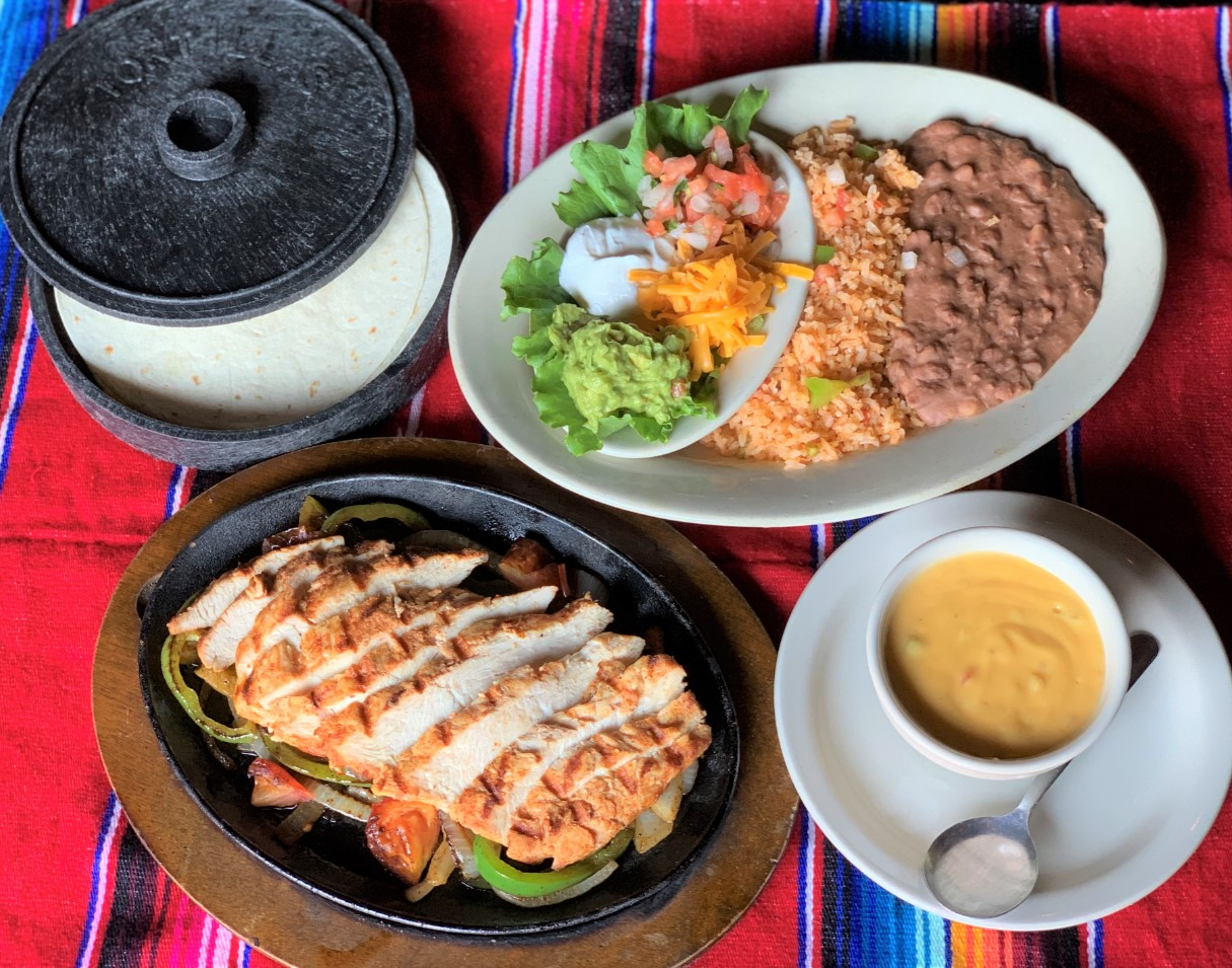 a spread of tex mex food on a serape-covered table, including chicken fajitas, flour tortillas, a plate of beans and rice with guacamole, sour cream and pico, and a bowl of queso