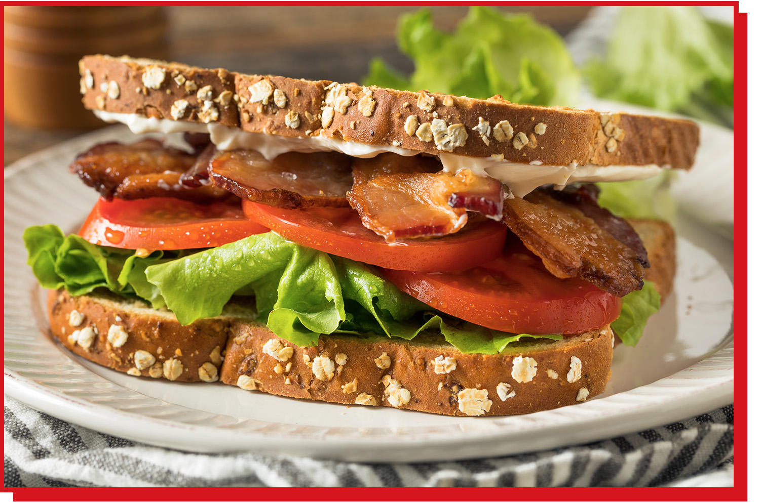 Sandwich with mayo, bacon, tomato, and lettuce layers between bread.