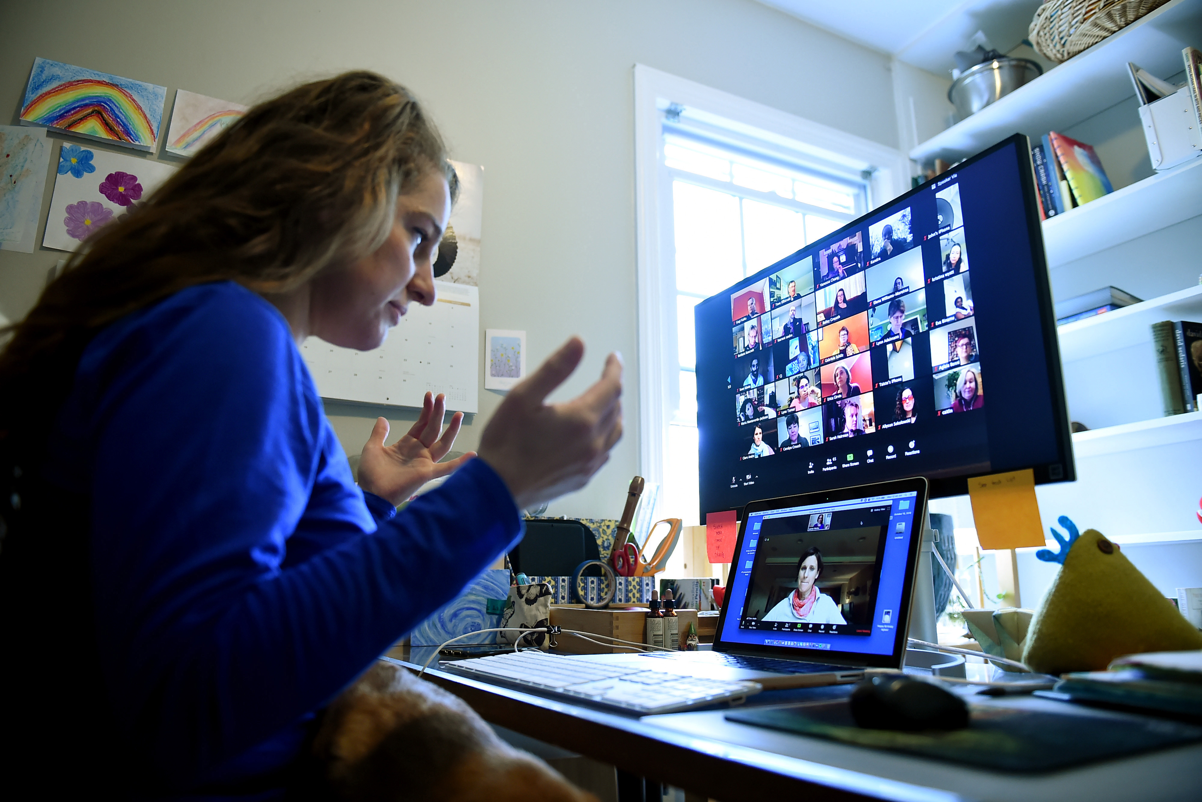 A teacher seated at a desk looks into a laptop and screen during remote learning.