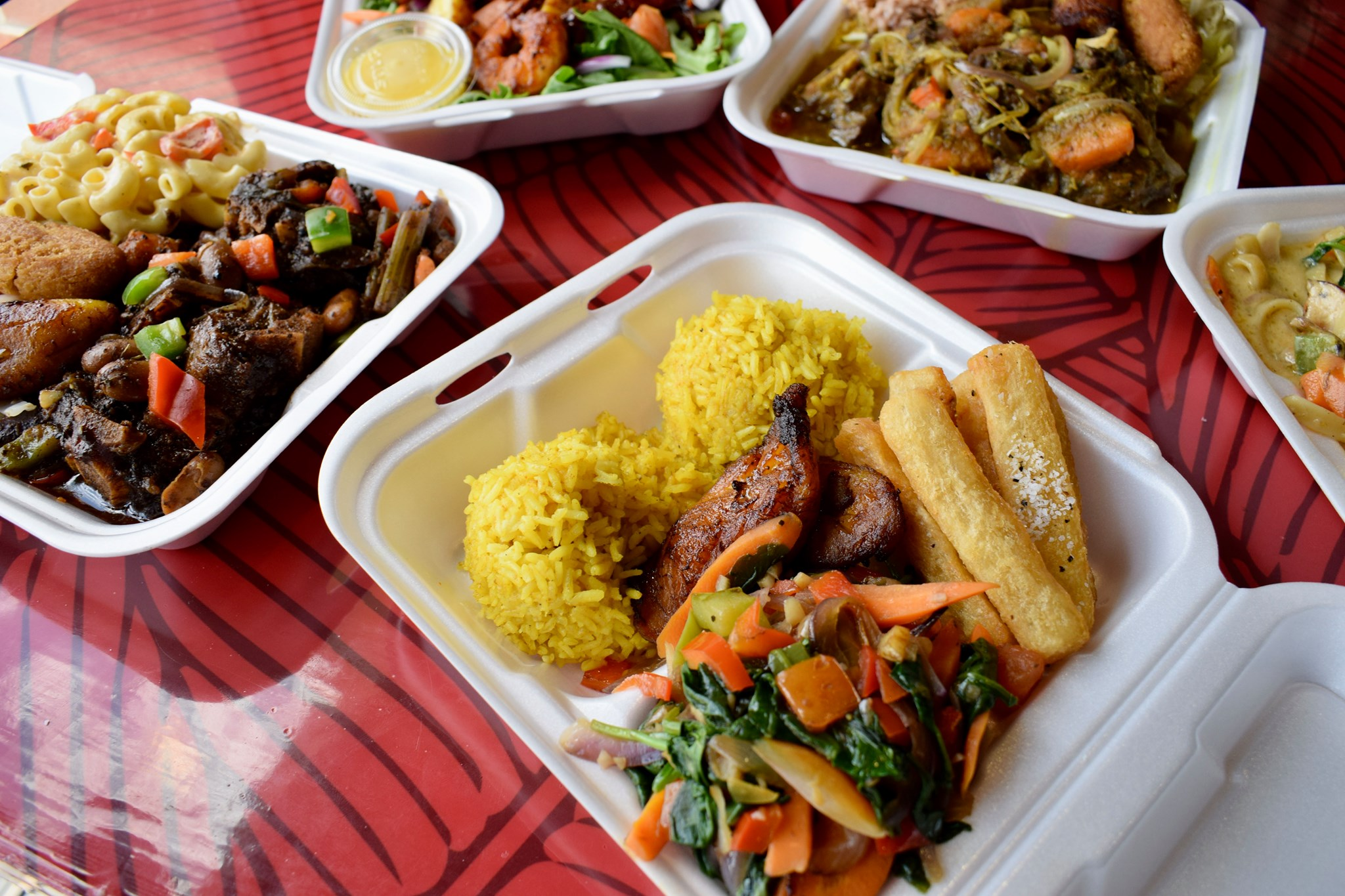 Takeout dishes in Styrofoam containers with rice, vegetables, meats, and more.