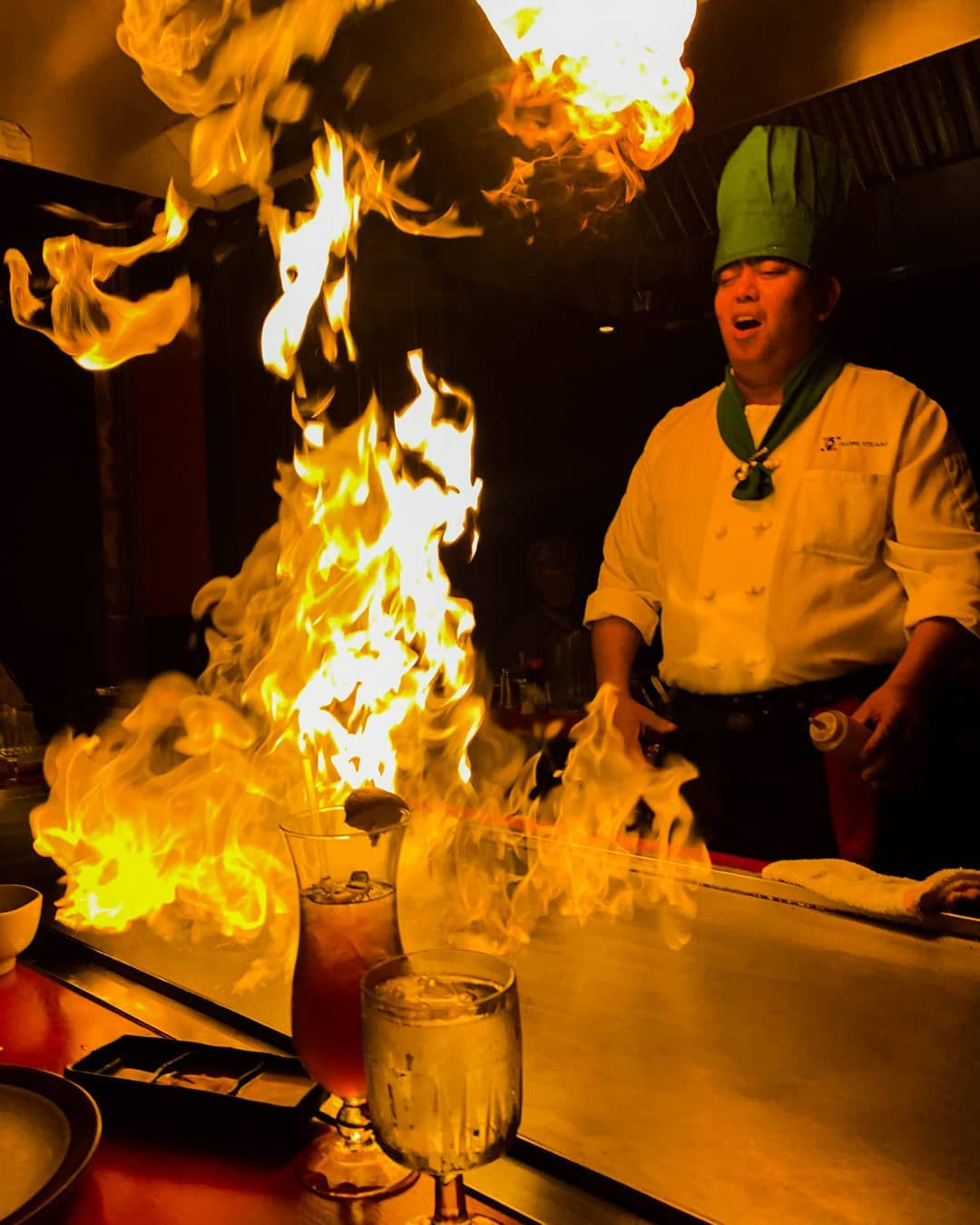 A hibachi chef in white coat and tall green chef's hat stands over a flaming hibachi grill