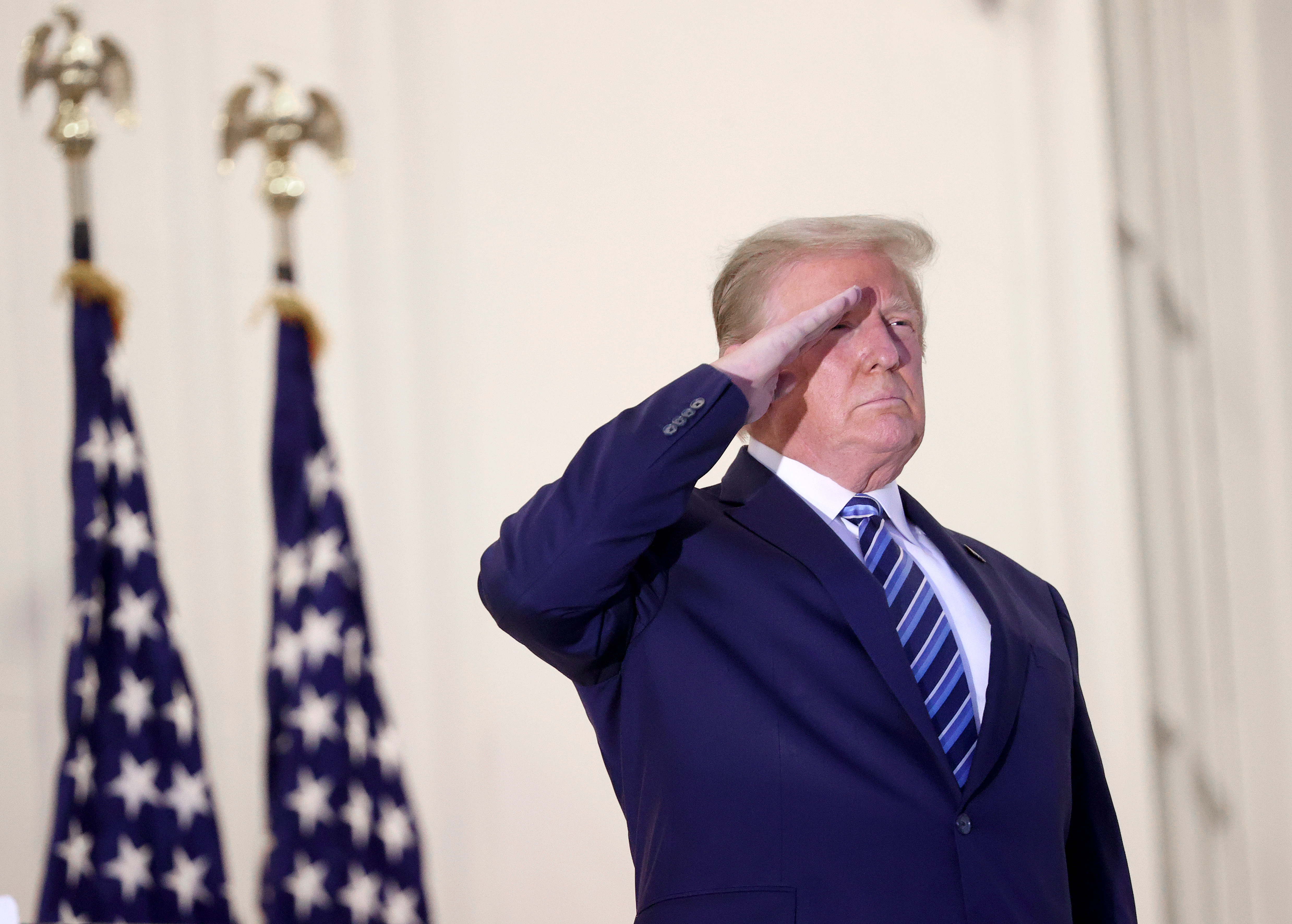 Wearing a navy suit and tie, Donald Trump salutes in front of a row of American flags outside the White House.