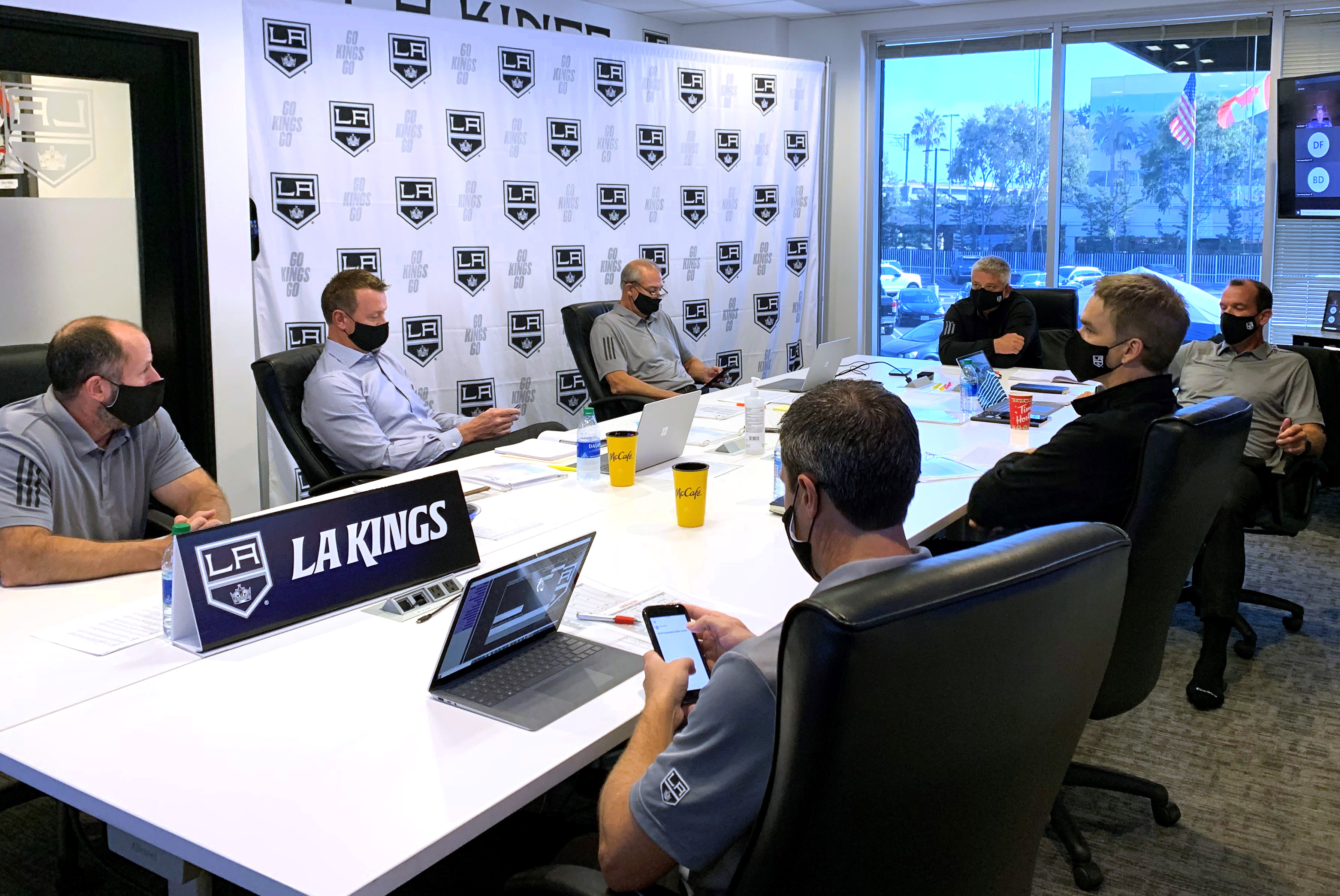 President Luc Robitaille, general manager Rob Blake, head coach Todd McLellan and Los Angeles Kings team personnel sit at their draft table during the first round of the 2020 NHL Entry Draft at the Toyota Sports Performance Center on October 06, 2020 in El Segundo, California. The 2020 NHL Draft was held virtually due to the ongoing Coronavirus pandemic.