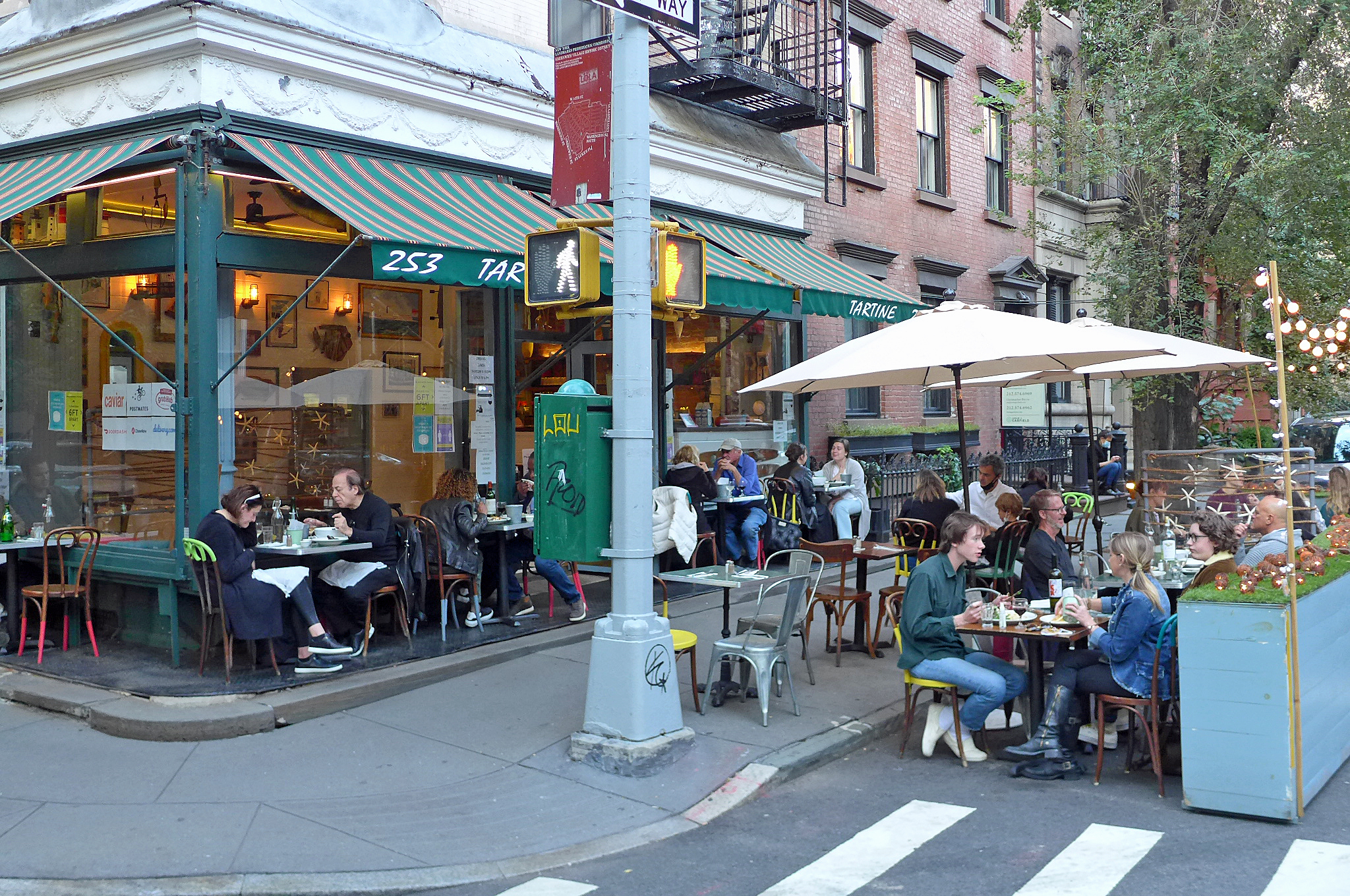 A corner restaurant with seating in the street covered by umbrellas.