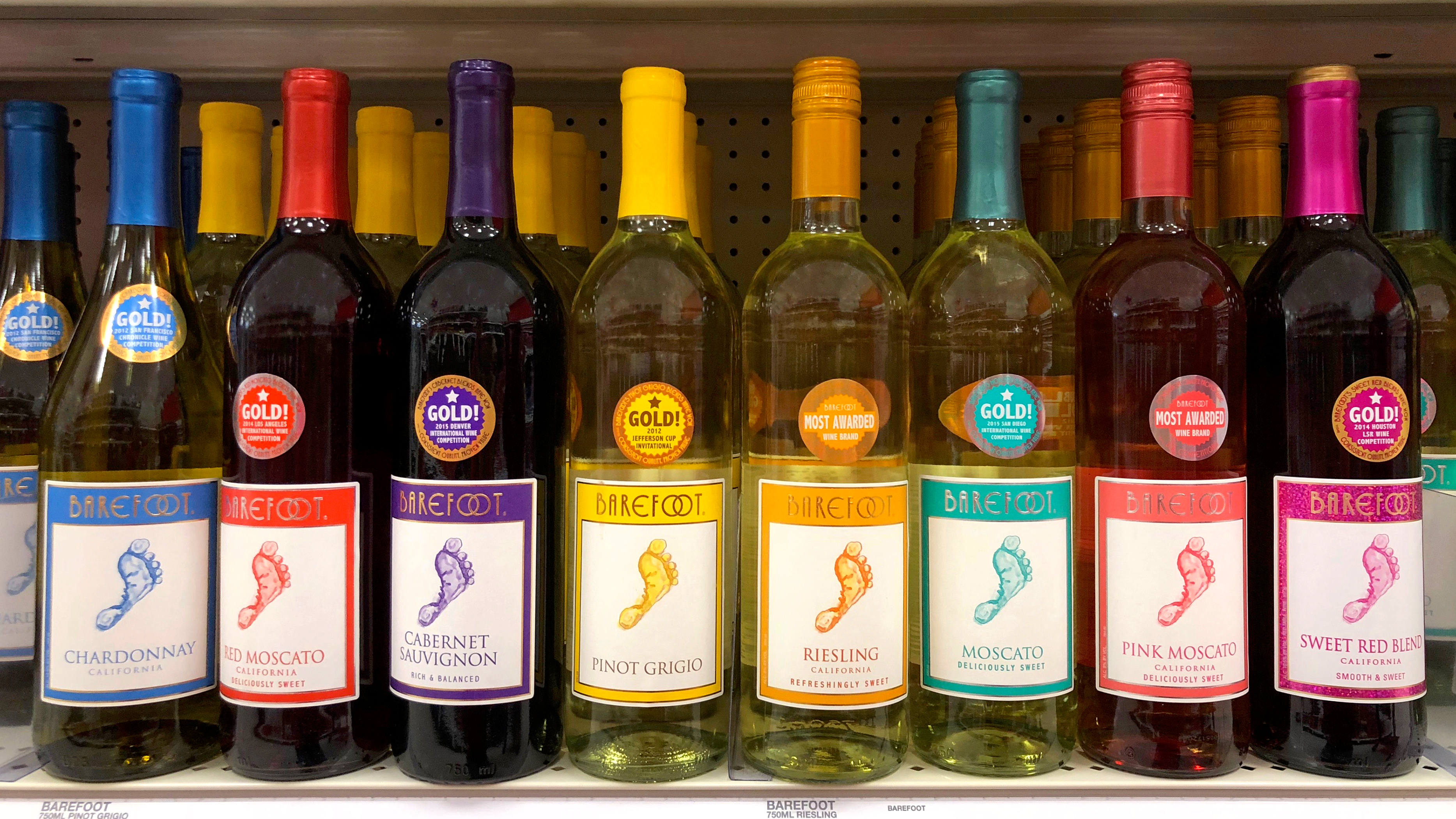 a row of wine bottles in different colors with labels that say barefoot