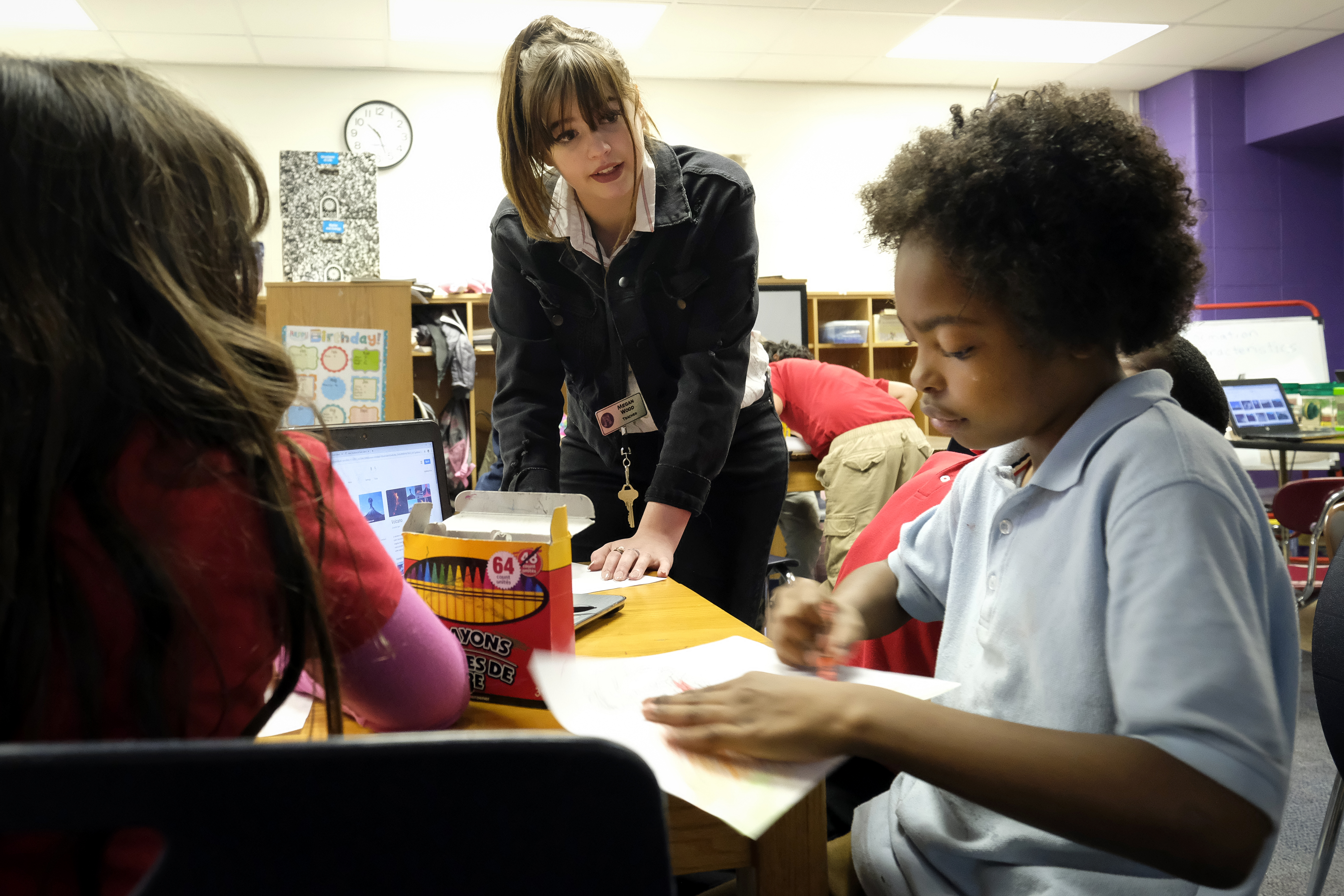 A teacher talks with students sitting at a table in a classroom at Thomas Gregg Neighborhood School, an elementary school in Indianapolis, Indiana.