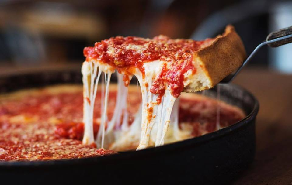 A slice of pizza being served from a pan.