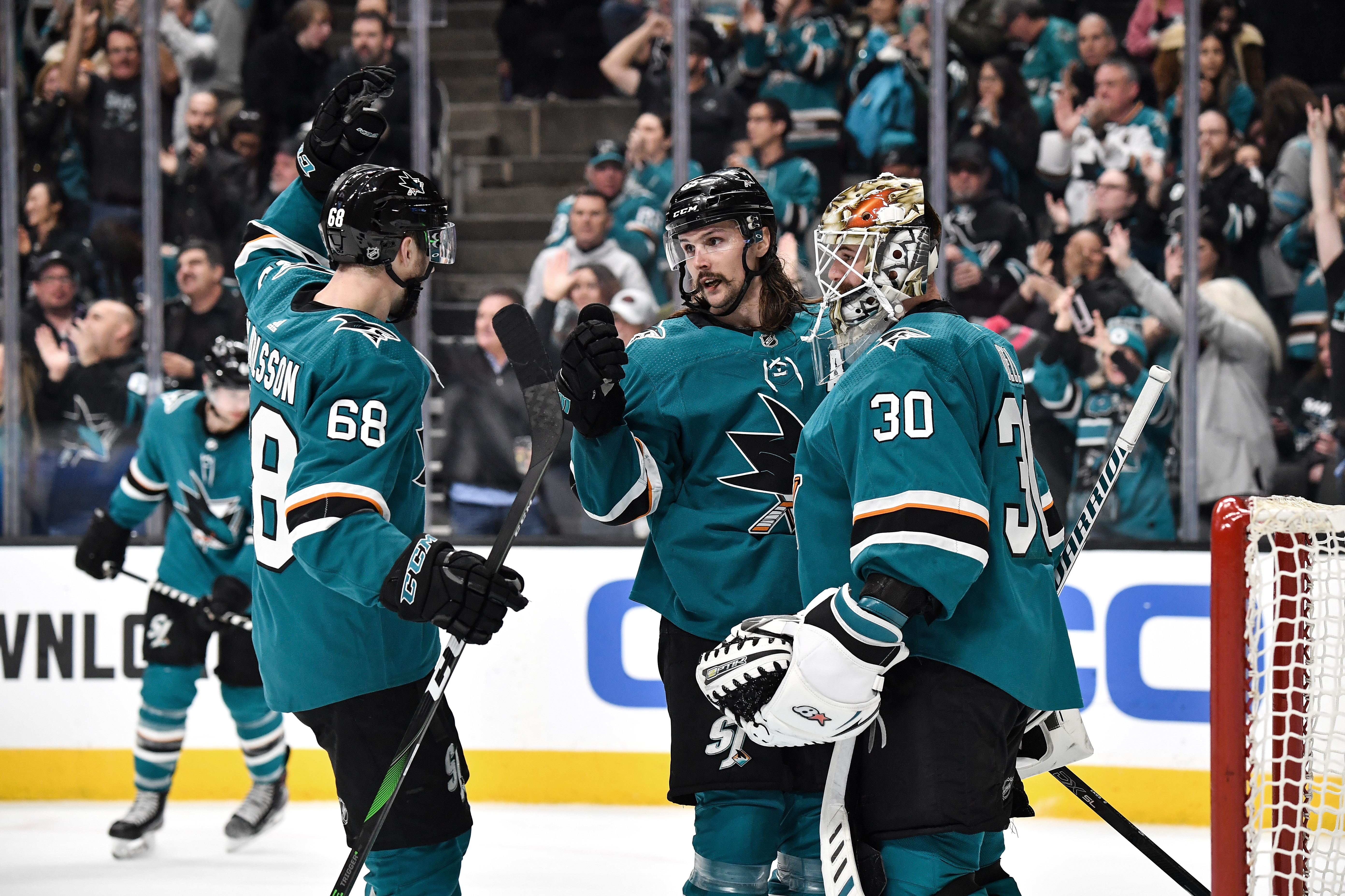 SAN JOSE, CA - JANUARY 11: Aaron Dell #30, Melker Karlsson #68 and Erik Karlsson #65 of the San Jose Sharks celebrate the win against the Dallas Stars at SAP Center on January 11, 2020 in San Jose, California.