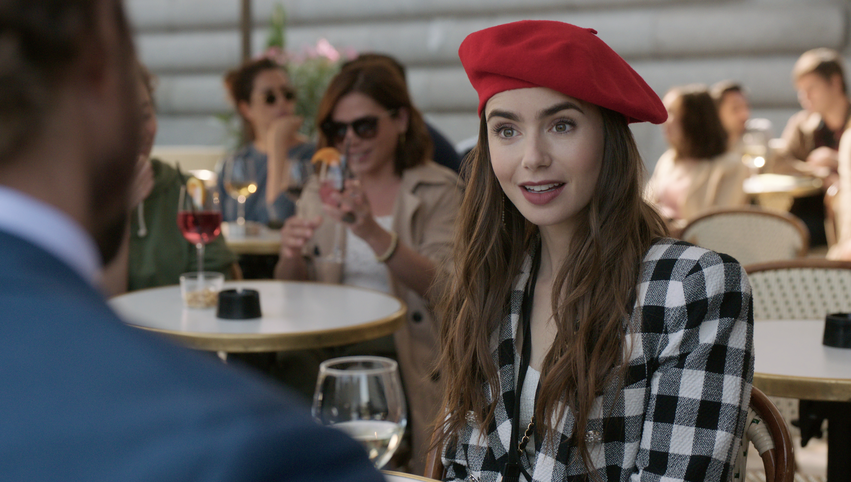 A young white woman with long brown hair wears a red beret and black-and-white plaid blazer while sitting at a crowded Paris sidewalk cafe with a glass of white wine.