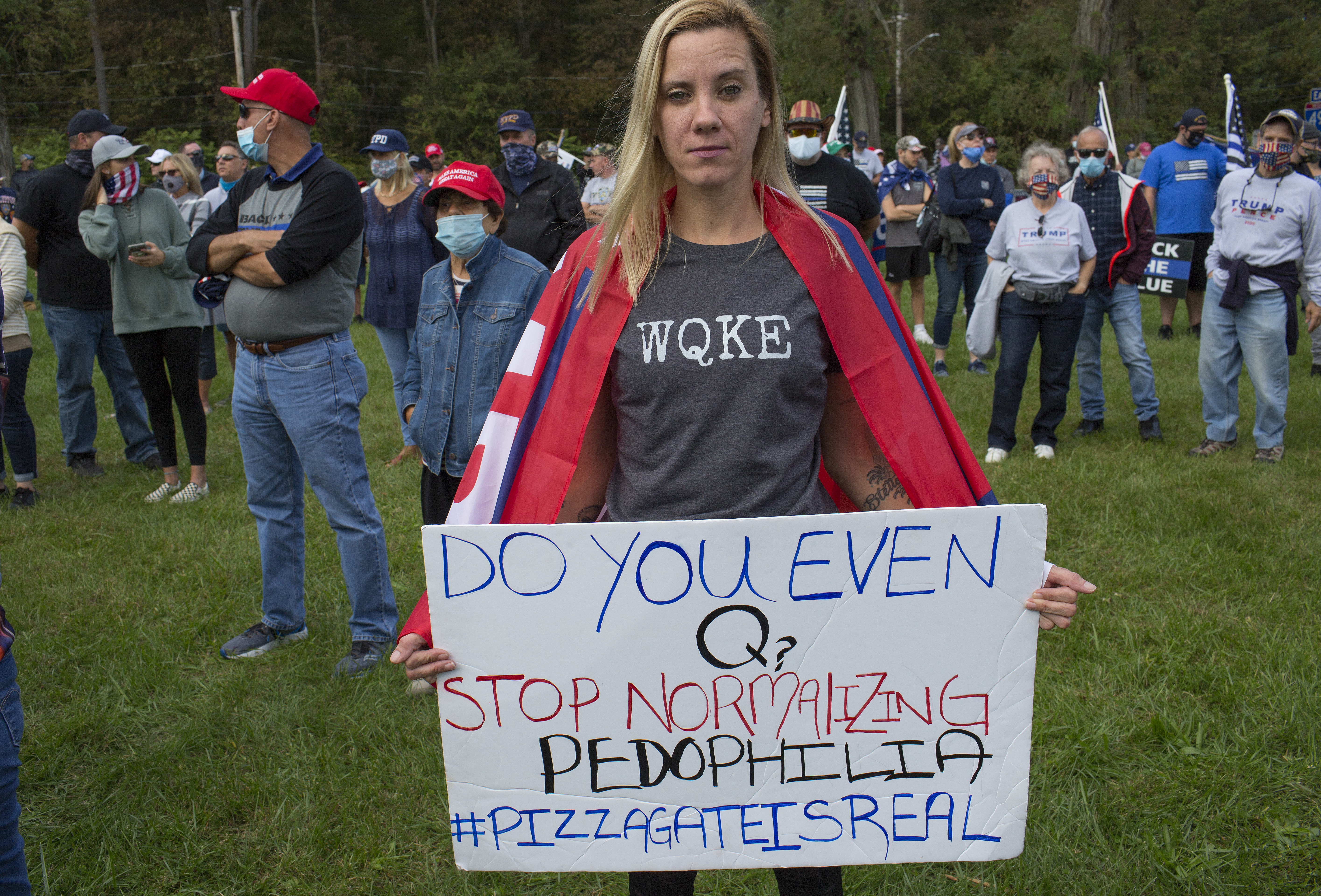 """A QAnon supporter wearing a shirt that reads """"WQKE"""" and carrying a sign that reads, """"Do you even Q? Stop normalizing pedophilia #pizzagateisreal."""""""