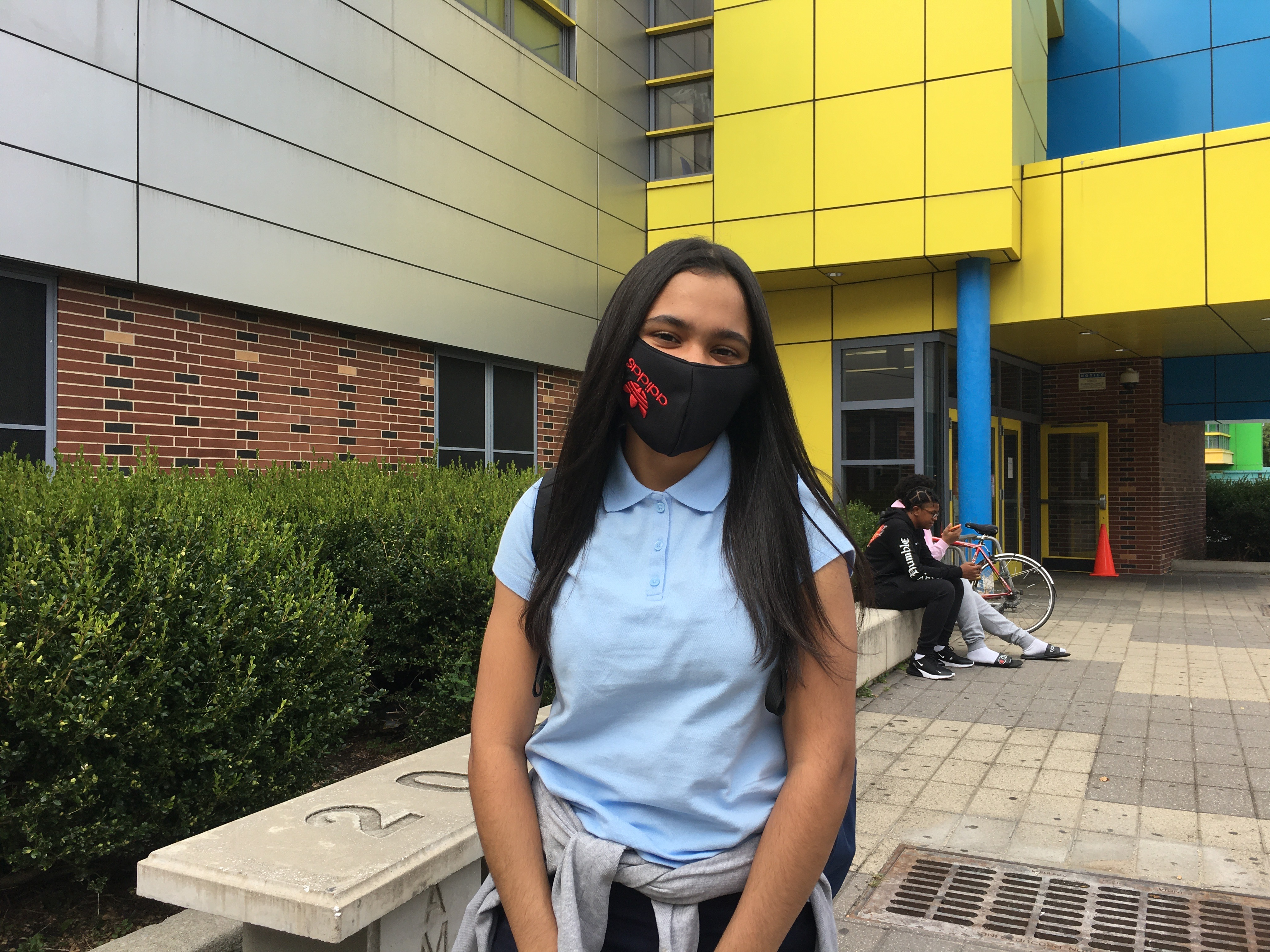 Ashanty Peralta wearing an Adidas face mask standing outside Urban Assembly School for Applied Math and Science.